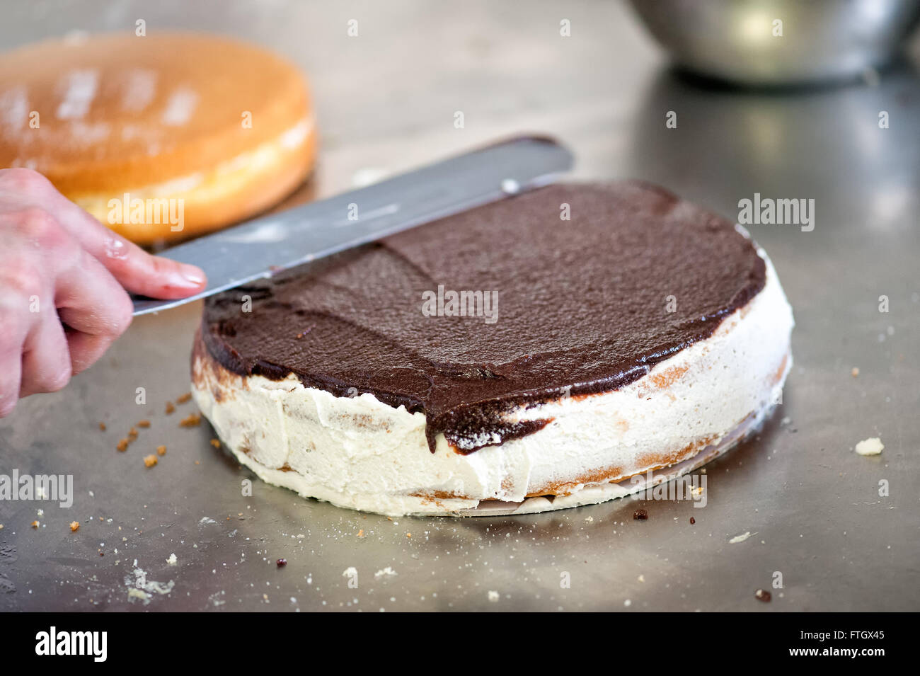 Baker or pastry chef icing a freshly baked chocolate cake using a large flat spatula as he works in a bakery - Stock Image