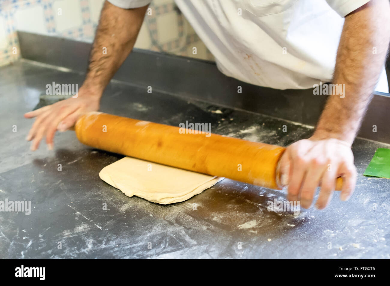 Close Up Action Shot of Male Baker Rolling Out Dough with Wooden Rolling Pin on Metal Surface in Professional Bakery - Stock Image