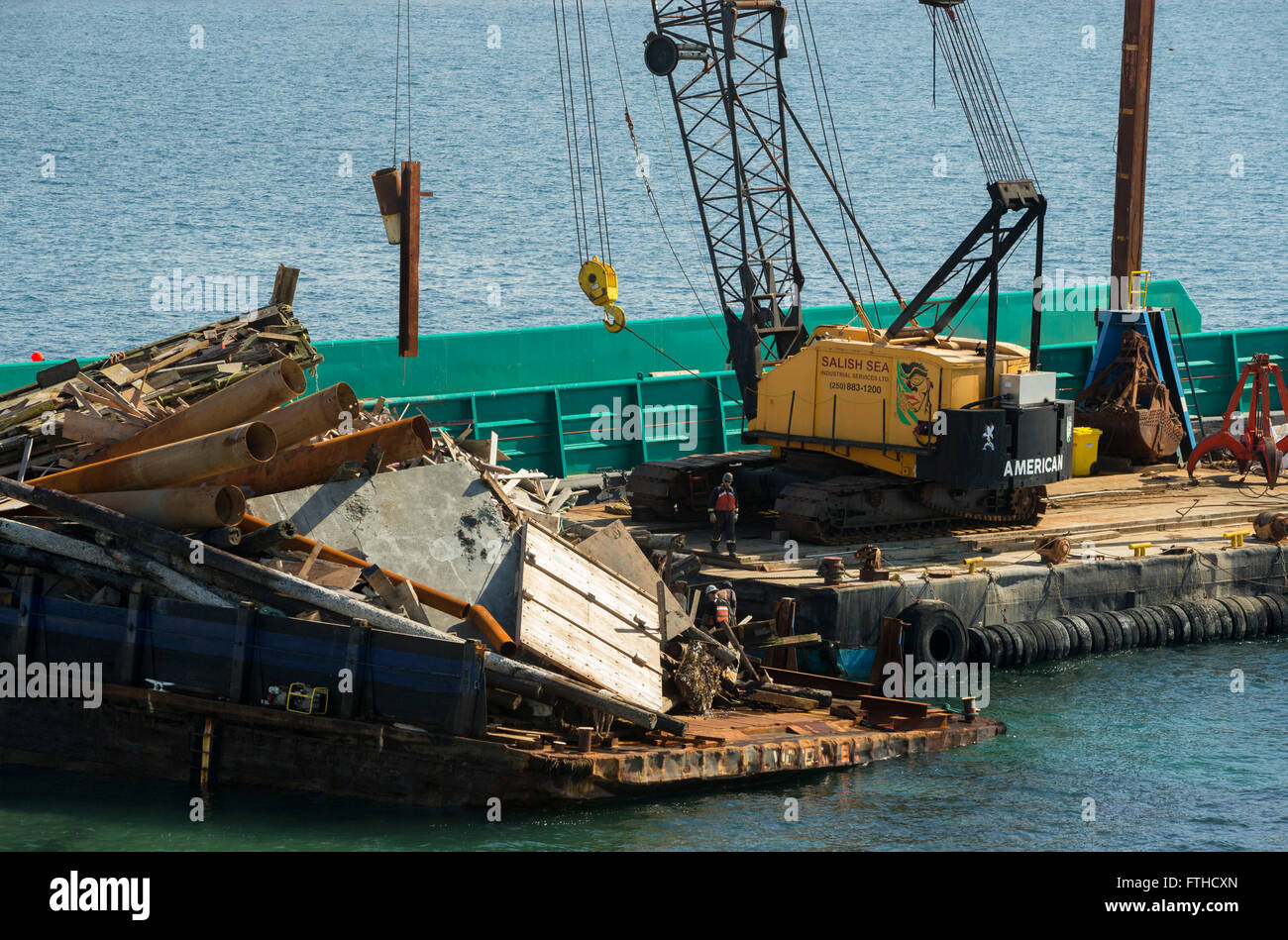 Beached stranded barge with load of junk being unloaded by large crane at Clover Point beach-Victoria, British Columbia, - Stock Image