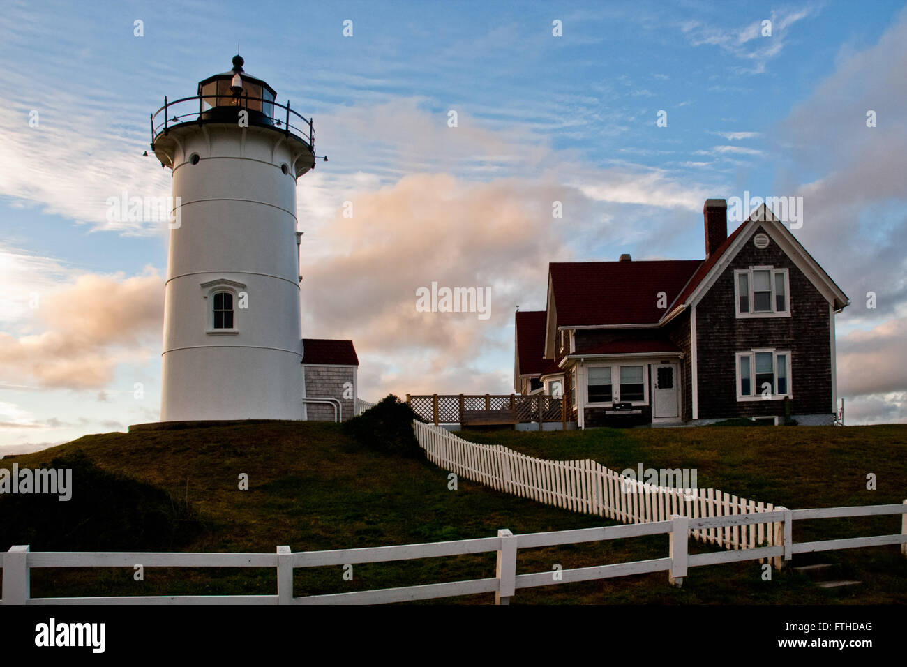 Sun sets behind Nobska lighthouse on Cape Cod and keepers building on a warm summer evening. Stock Photo