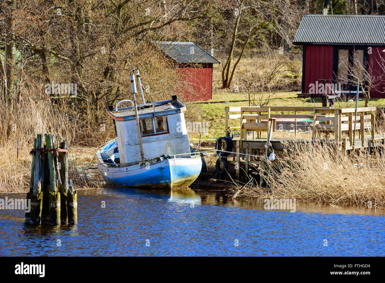 Old Fishing Boat Moored At Seaside Beside A Wooden Pier Close To A Stock Photo Alamy