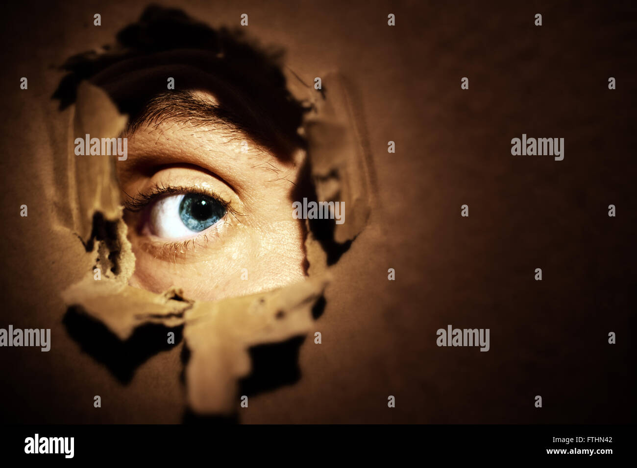 Male eyes spying through a hole in the wall - Stock Image