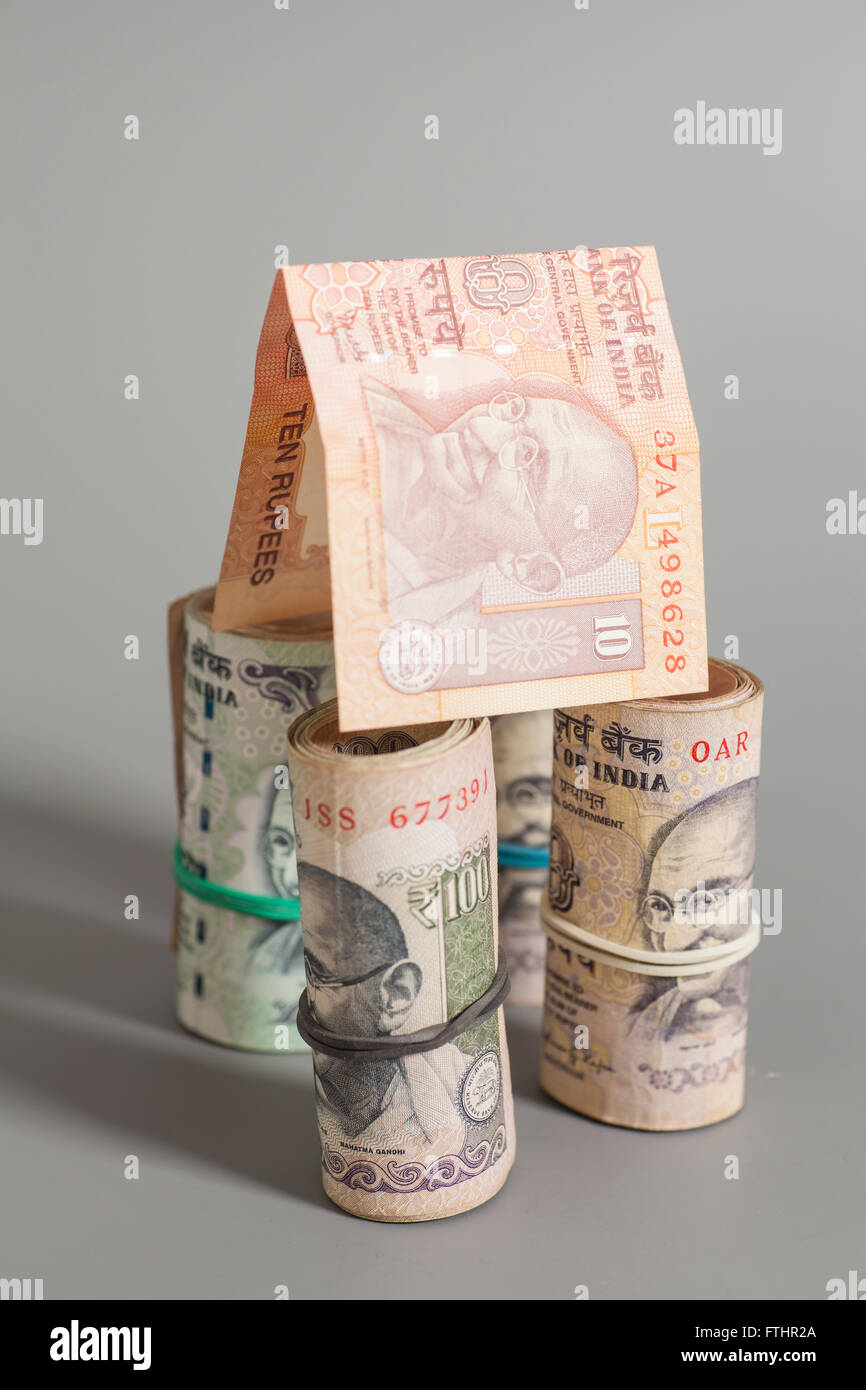House Made Roll of Indian rupee banknotes isolated on gray - Stock Image