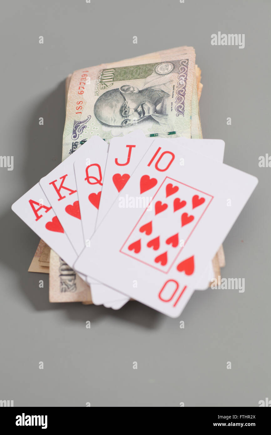 Royal Flush Playing Cards and Indian Currency Rupee bank notes isolated on gray background - Stock Image