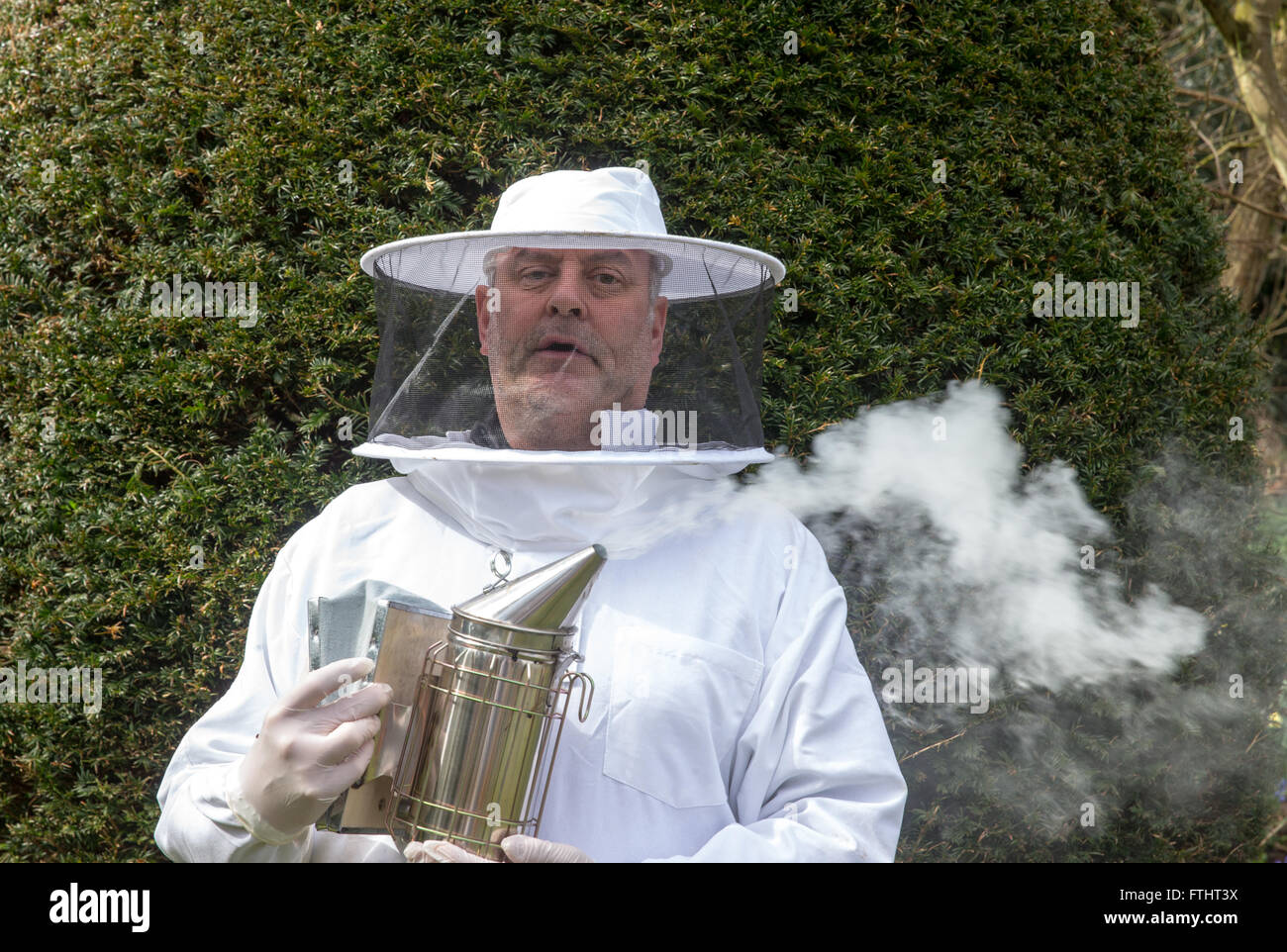 Portrait of a beekeeper with smoker - Stock Image
