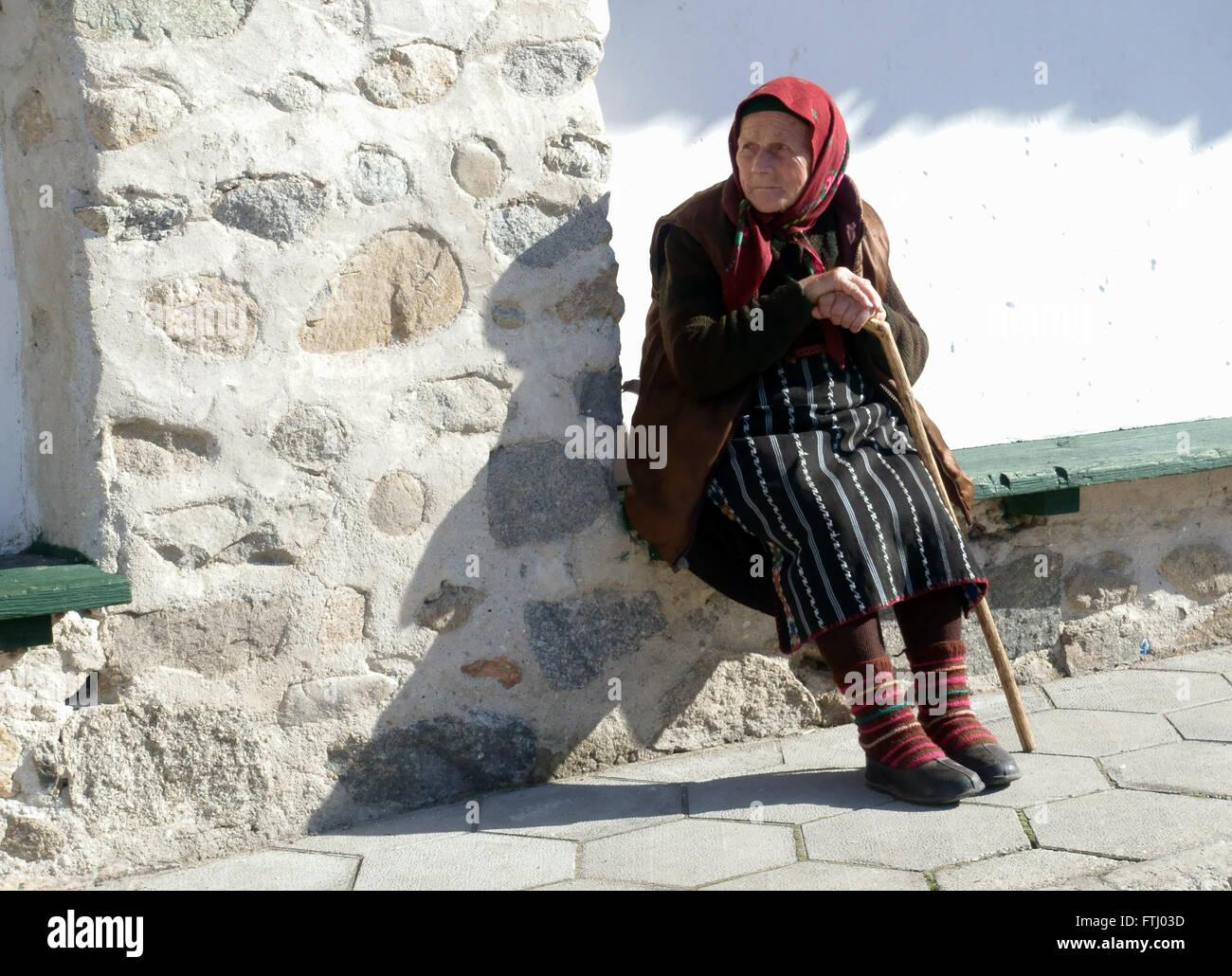 A Bulgarian lady from the village of Dobarsko enjoys the spring sunshine - Stock Image