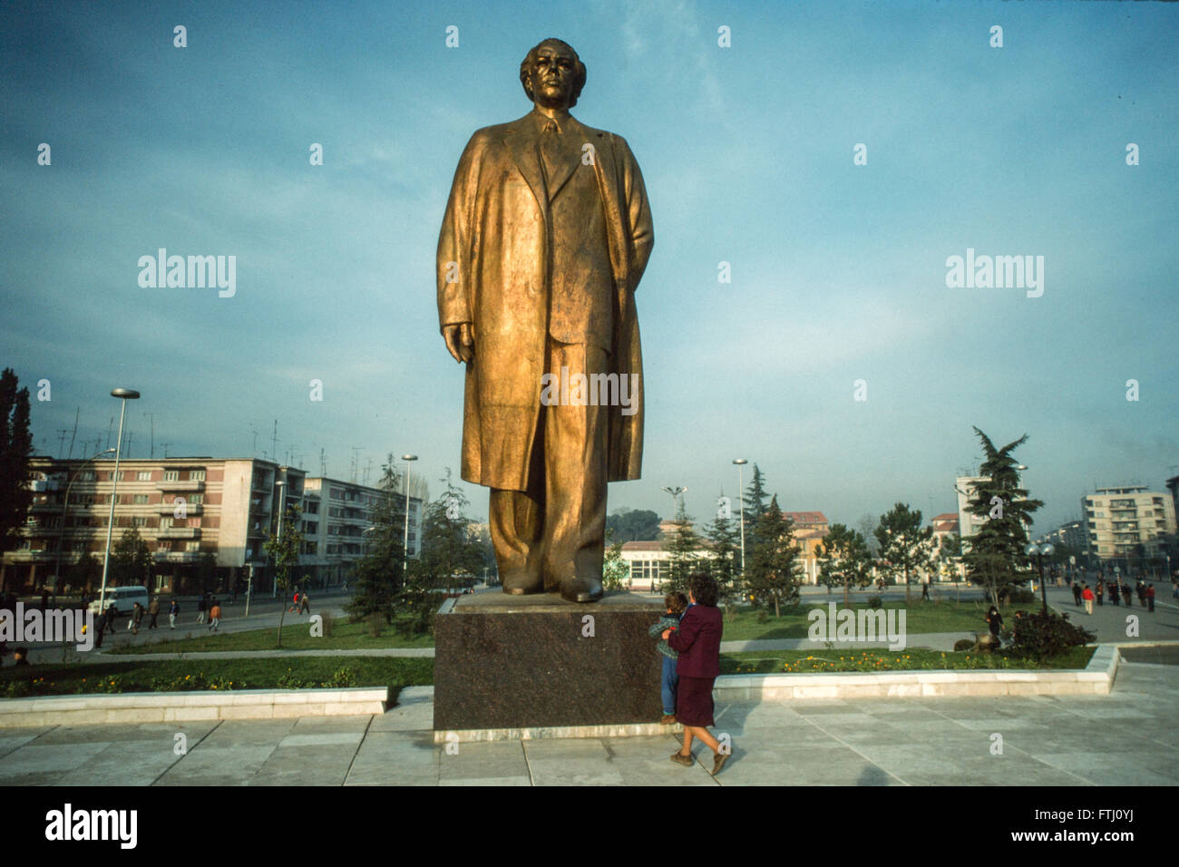 Young boy encouraged by his mother, kissing the feet of the statue of Enver Hoxha, the founder of the communist - Stock Image
