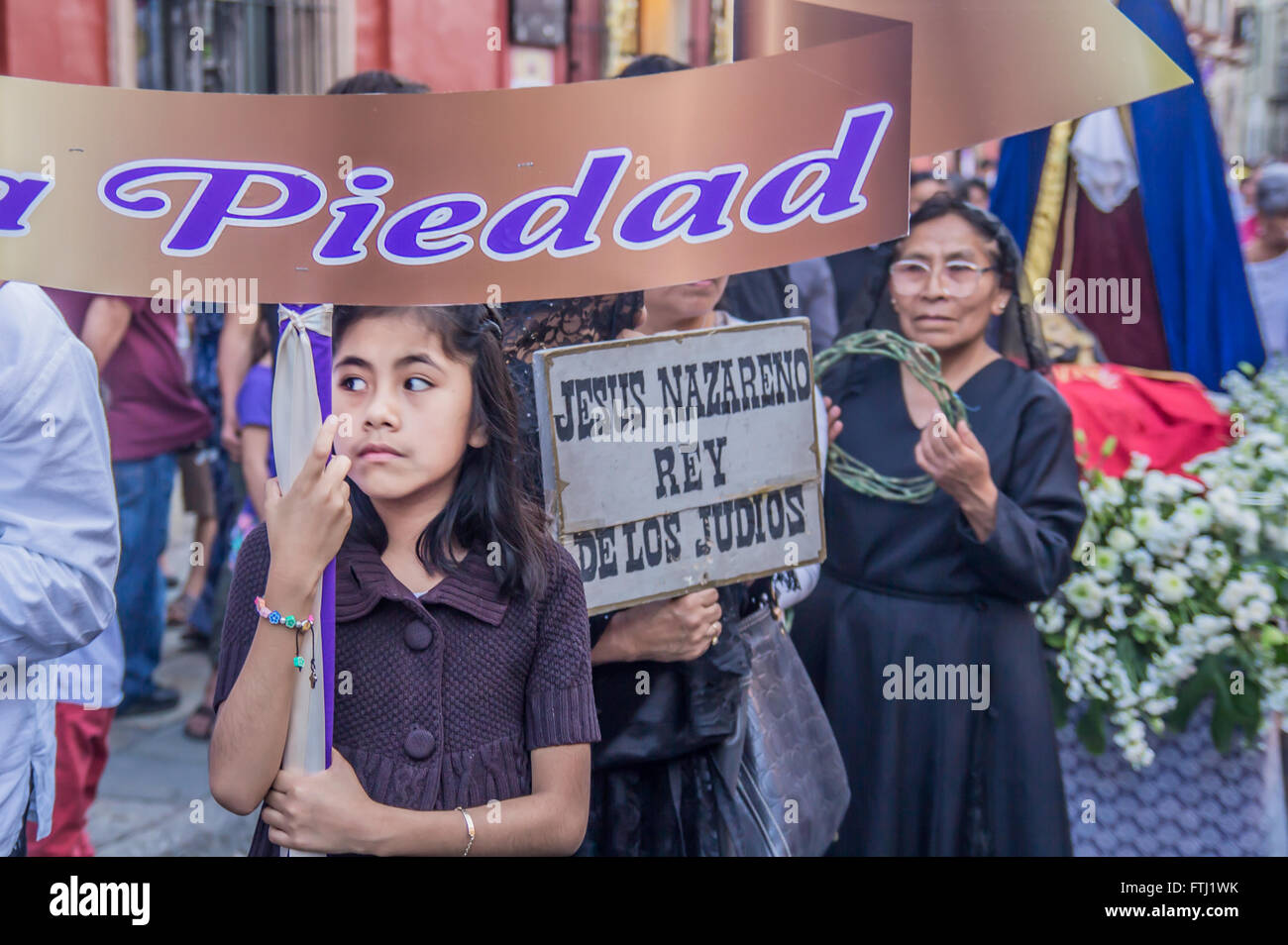 A little girl holding a placard saying 'Piety' at the Holy Friday procession in Oaxaca, Mexico. - Stock Image