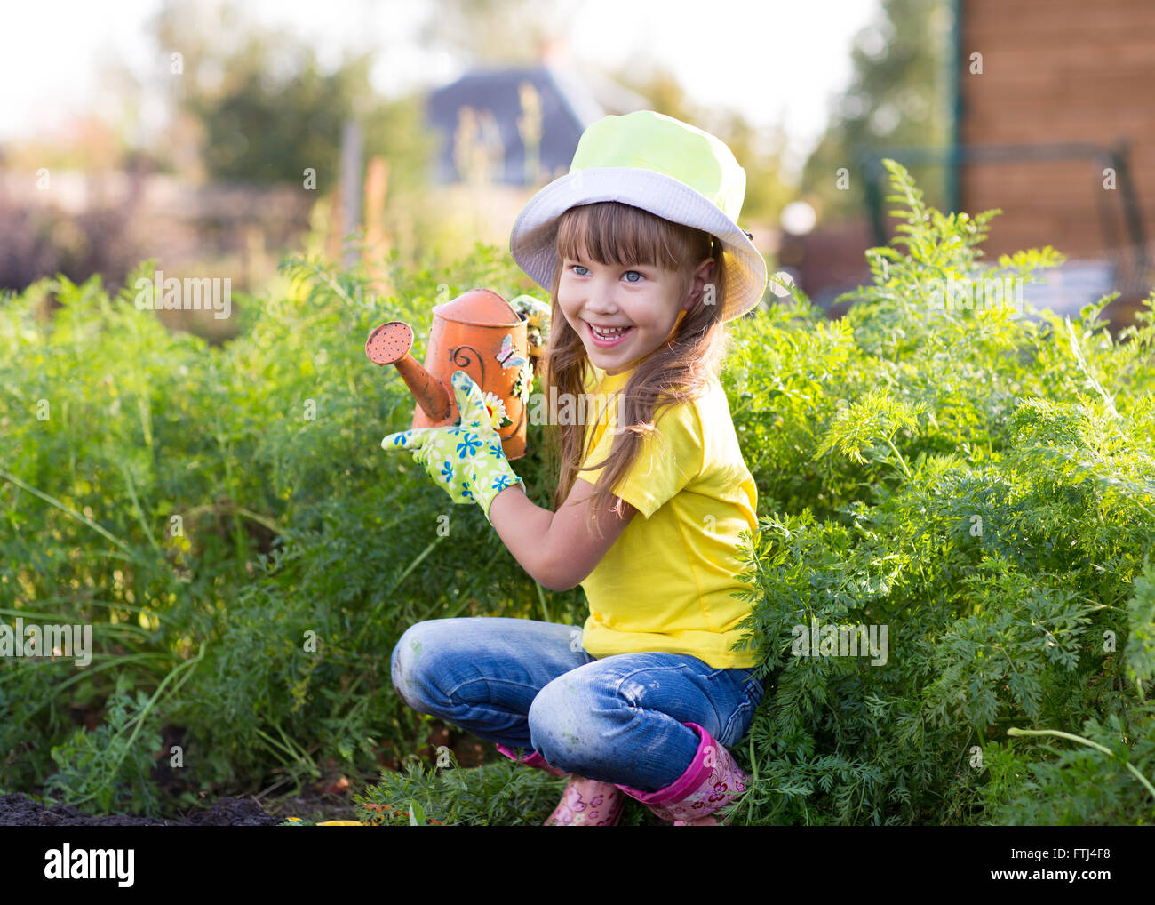 Little girl posing with watering can Stock Photo