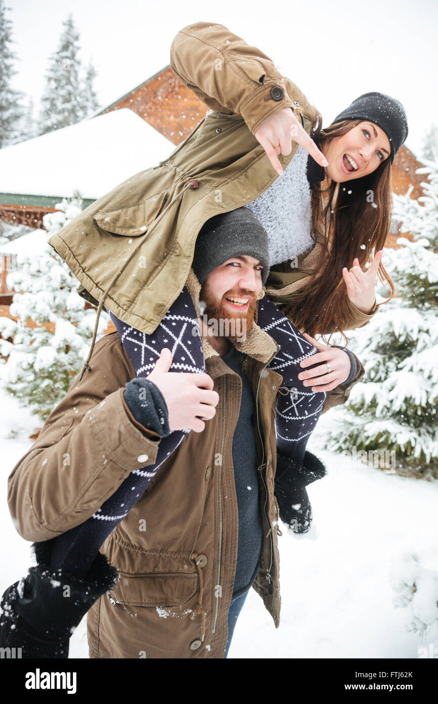 Beautiful young couple having fun and showing rock gesture in winter - Stock Image