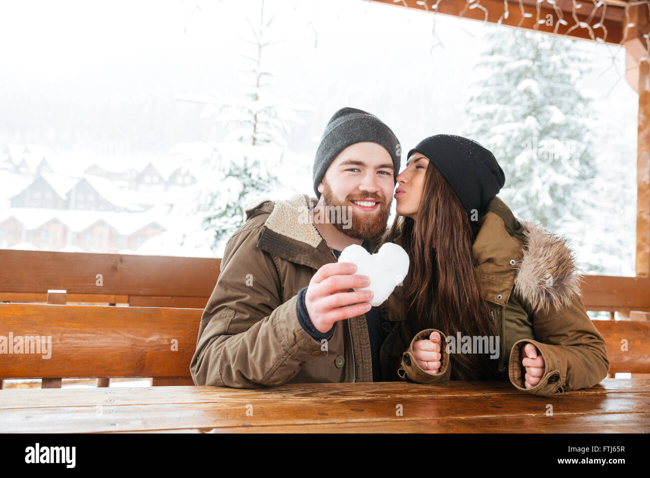 Happy young couple kissing in chalet patio and holding heart made of snow in winter Stock Photo