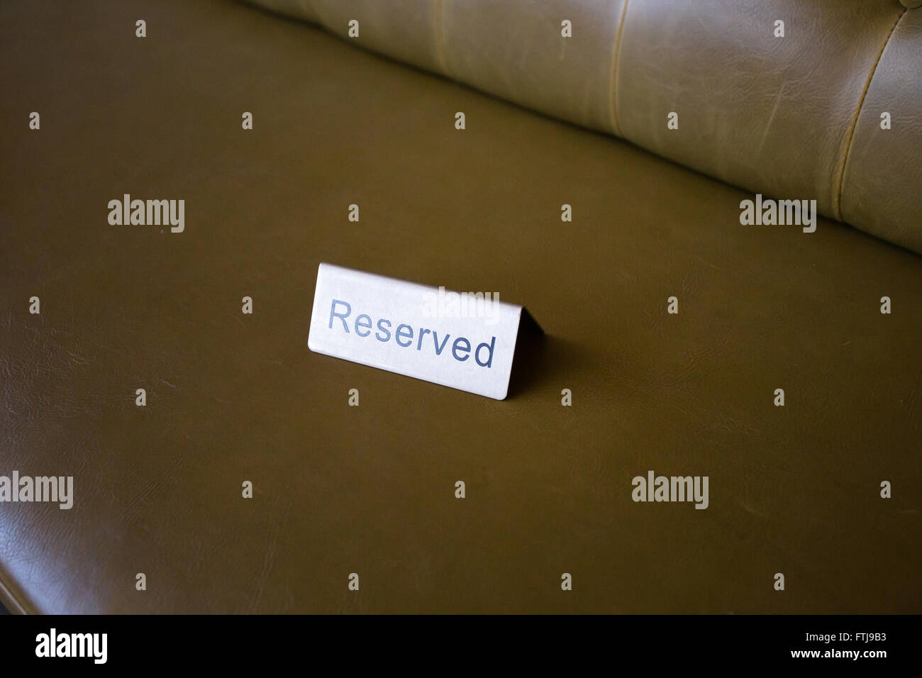 Reserved seats at a wedding ceremony and reception shown with this metal tag. - Stock Image