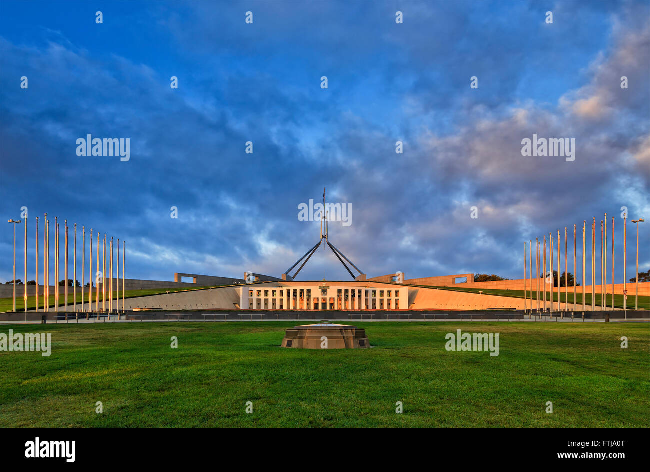 green lawn and tall flag poles with flags in front of new Parliament house in Canberra at sunrise. Australian Capital - Stock Image