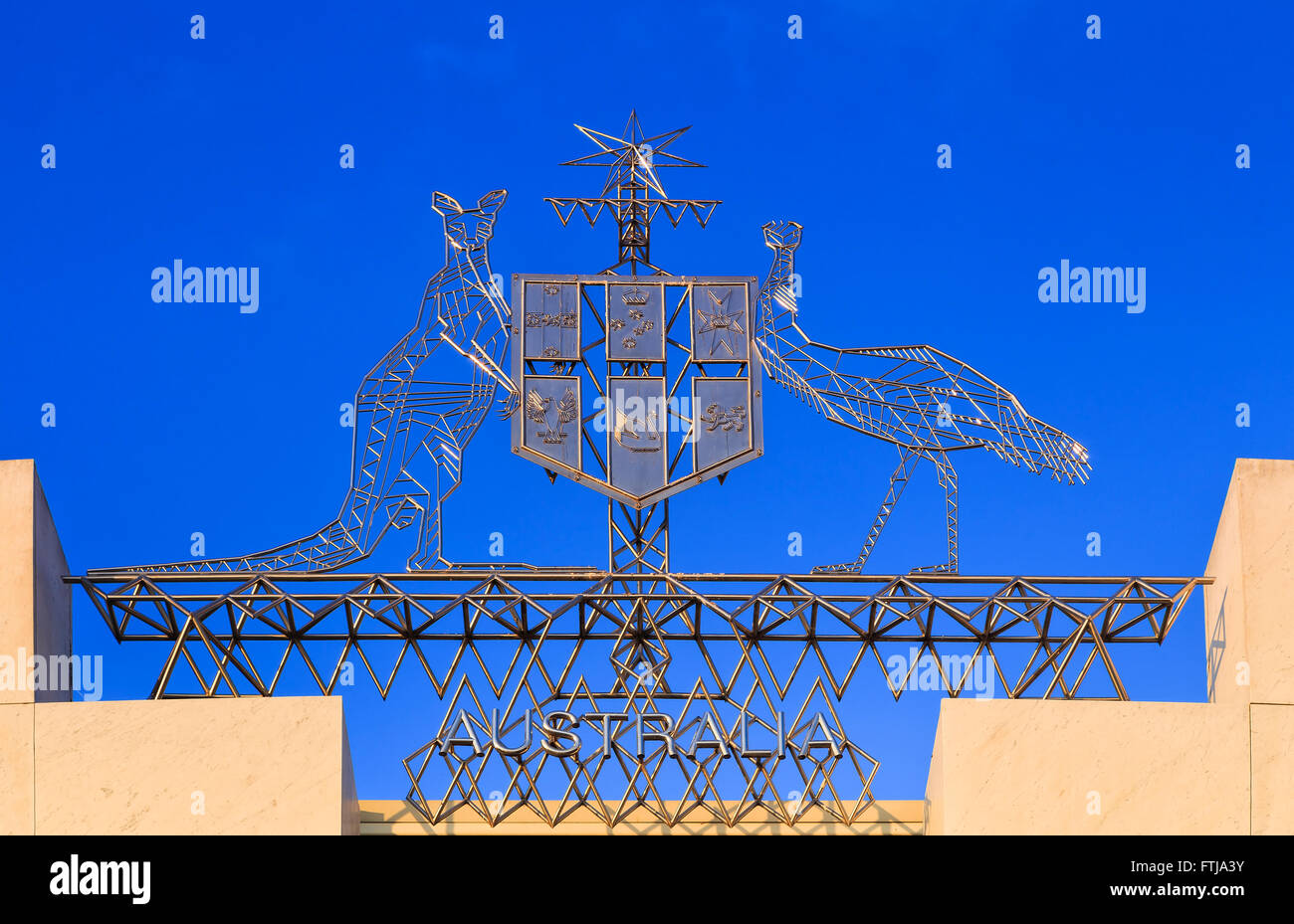 Australian national coat of arms on top of the New parliament house in Canberra against blue sky on a sunny day - Stock Image