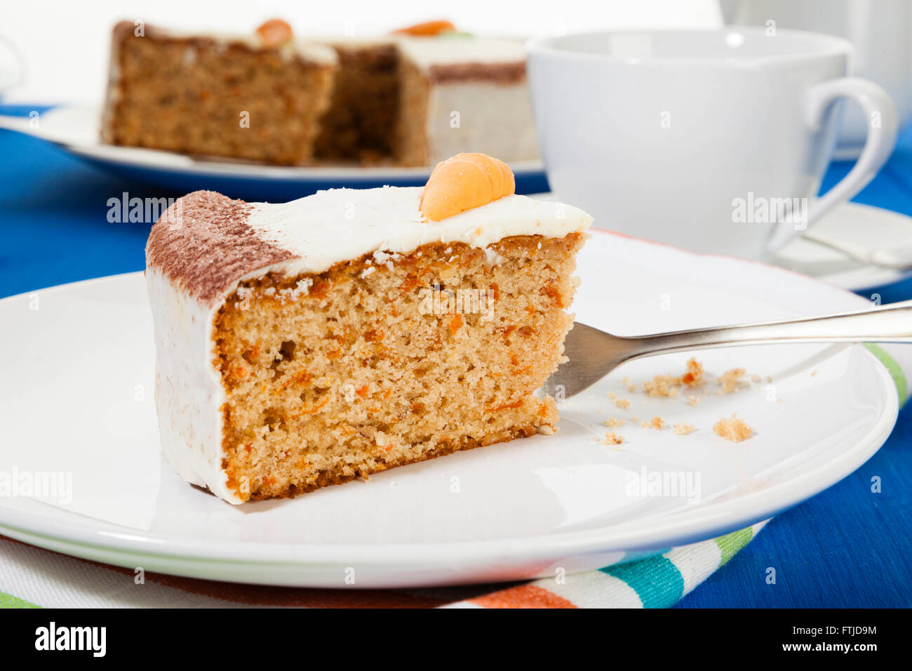 Piece of Carrot cake on a plate, on coffee table - Stock Image