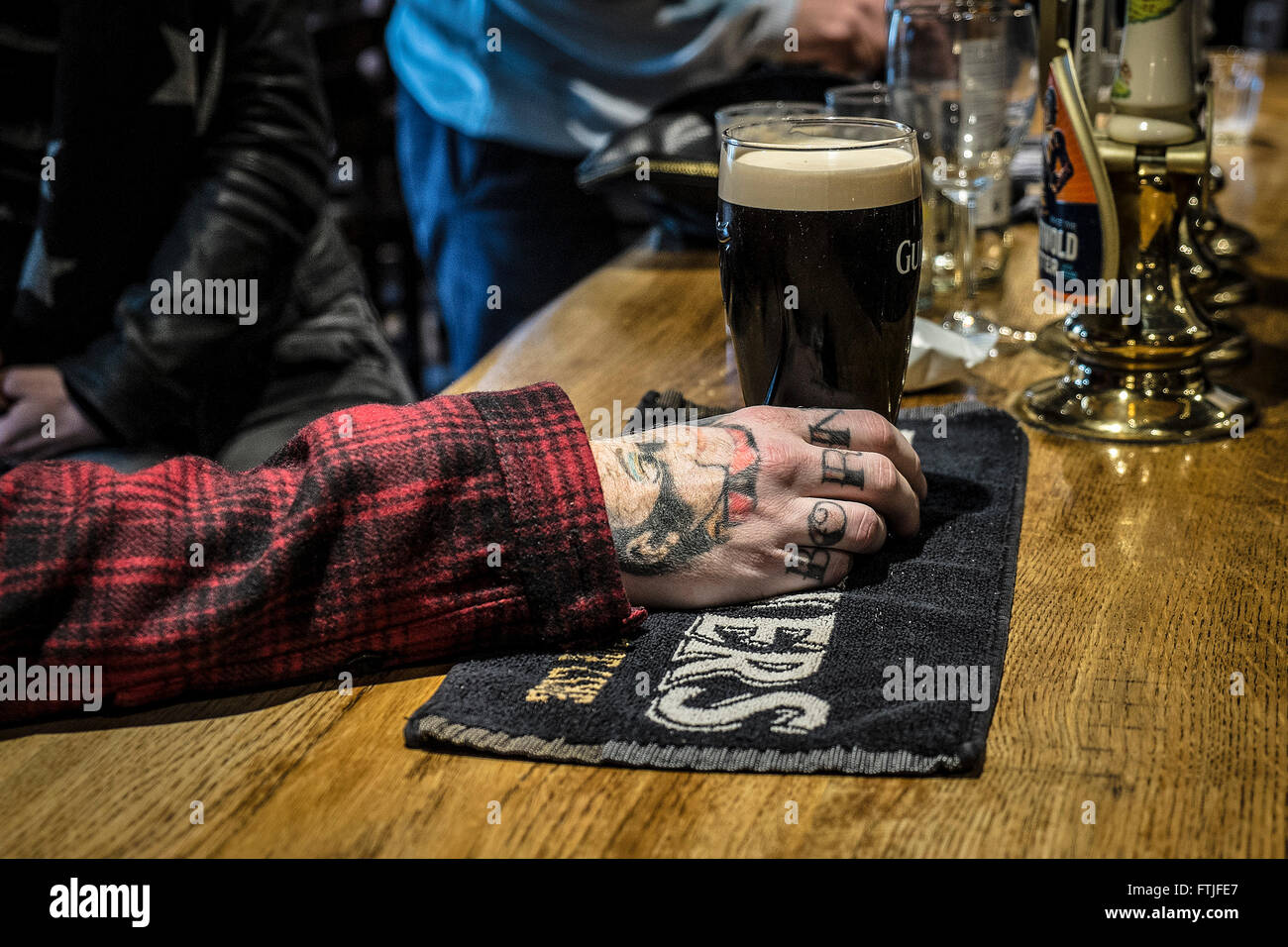 A customer's tattooed hand holding a pint of Guinness in a traditional English pub in Essex. - Stock Image