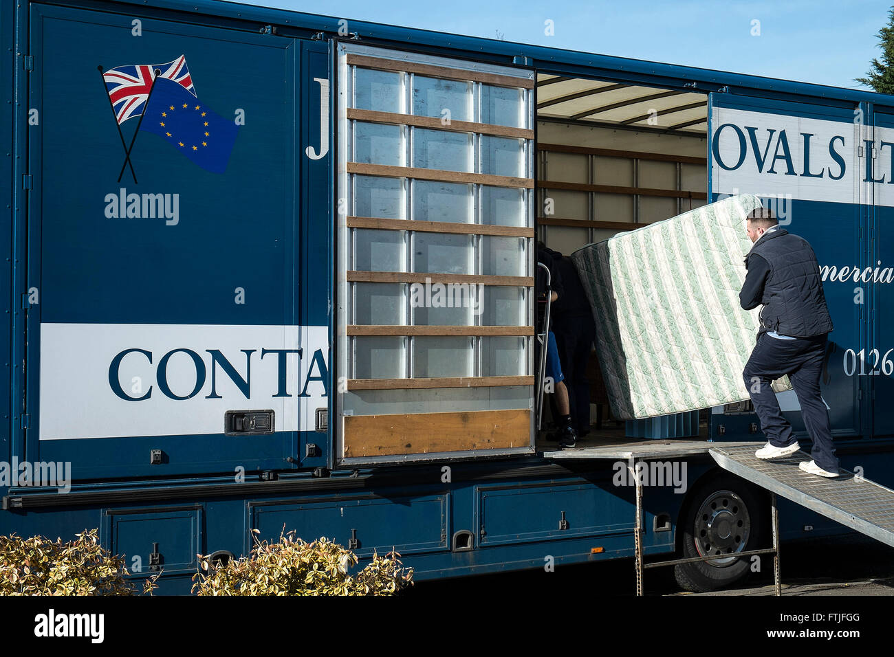 Removal man loading  a mattress into a removal van. - Stock Image