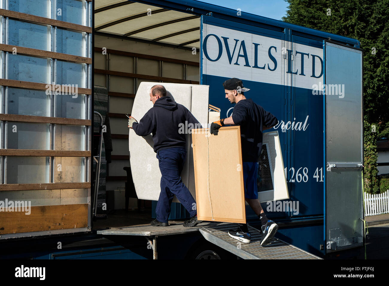 Removal men loading household items into a removal van. - Stock Image