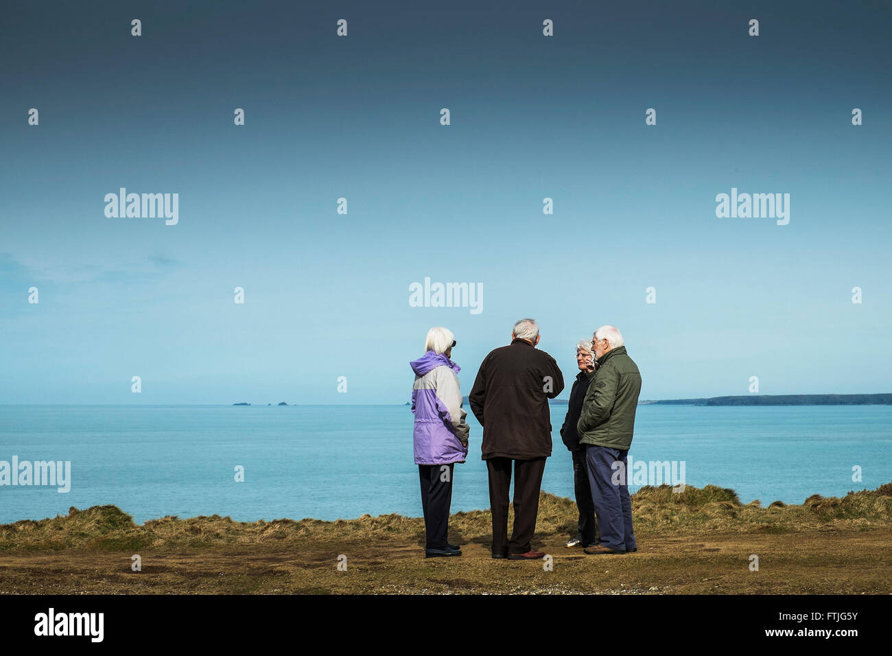 Two grey haired couples in conversation on Pentire east in Newquay, Cornwall - Stock Image
