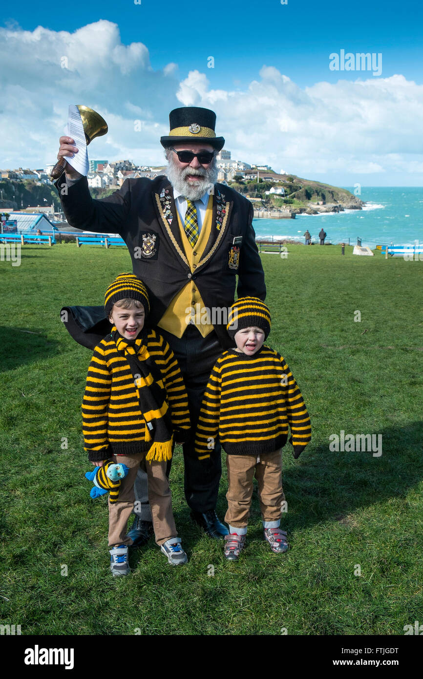 David Bradshaw, Newquay Town Crier stand with Morgan and Alfie as they celebrate St Piran's Day in Newquay, - Stock Image
