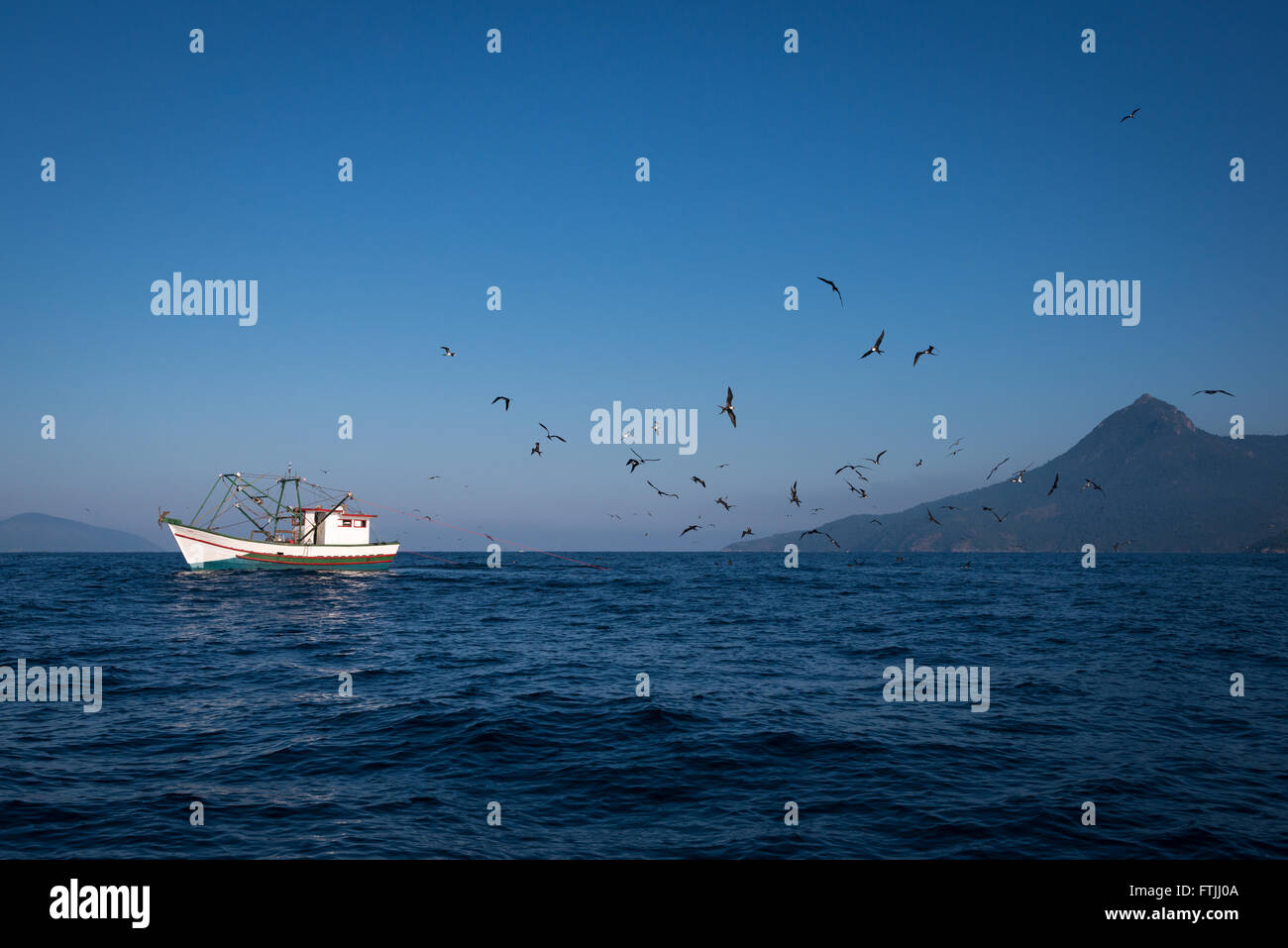 A fishing boat dragging a shrimp net off Ilhabela, SE Brazil. Birds like boobies and frigatebirds are following - Stock Image