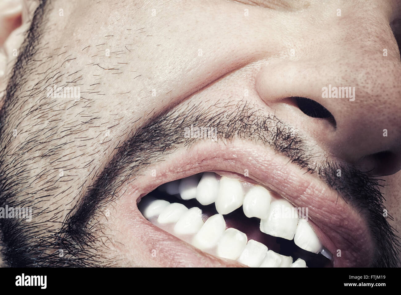 Male mouth with bared teeth close-up - Stock Image