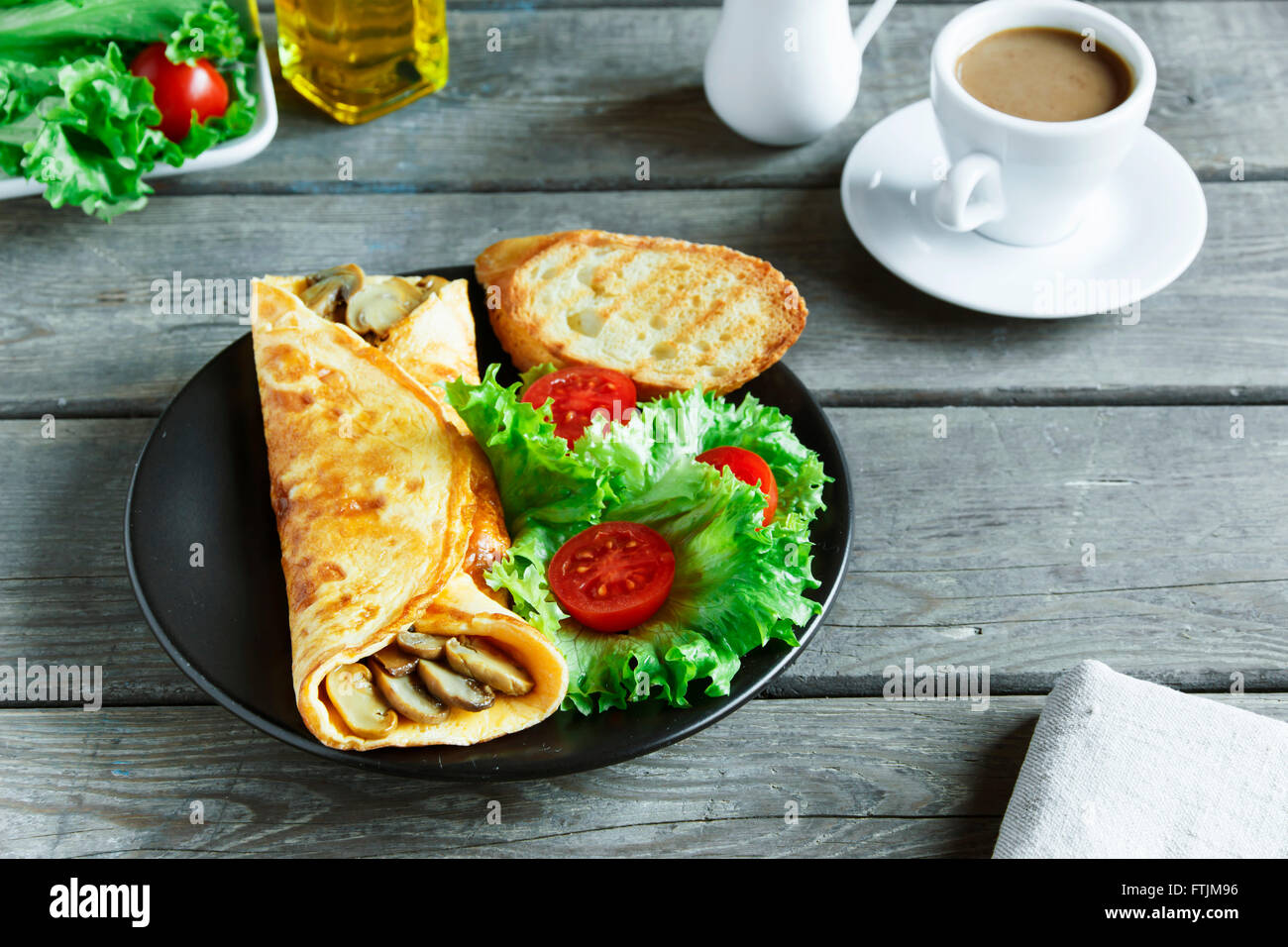 omelet with mushrooms on a plate with salad and tomato - Stock Image