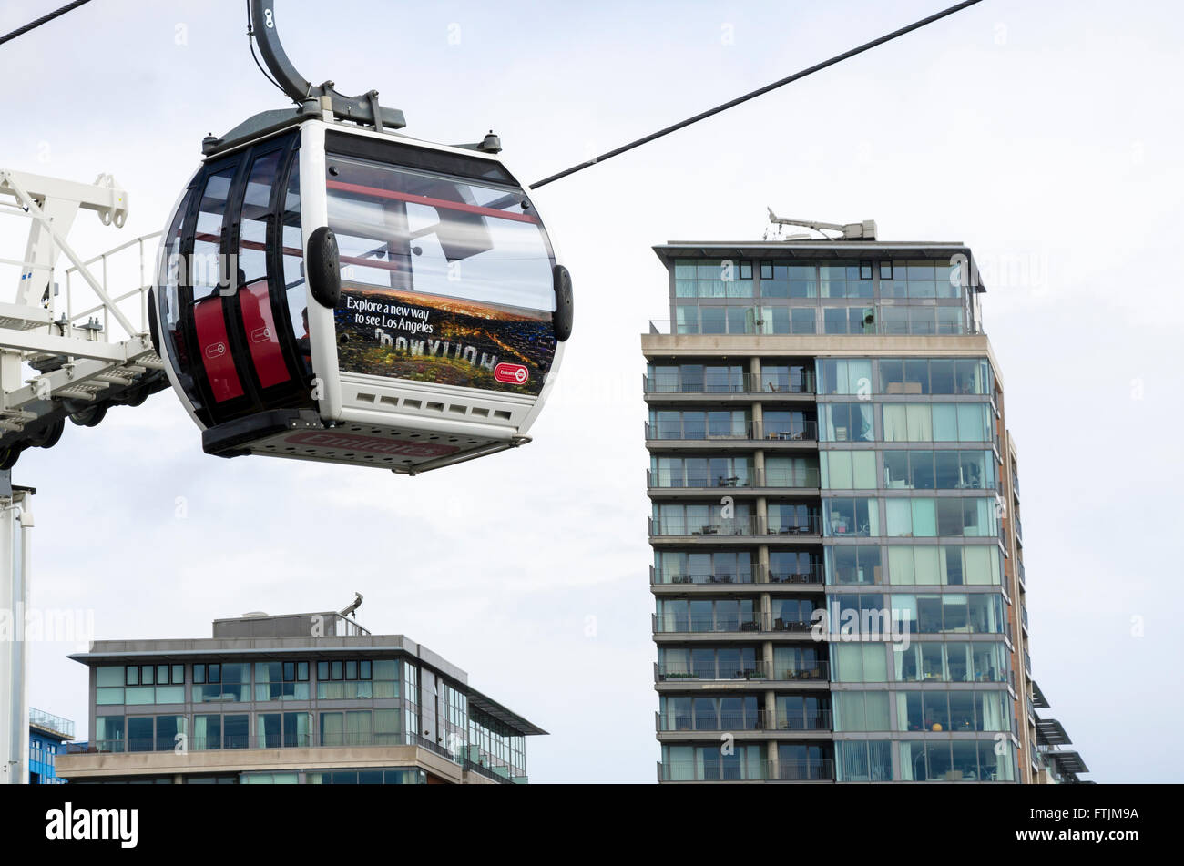 A cable car on the Emirates Air Line from Royal Victoria Docks to the O2 Dome goes past a tower block. - Stock Image