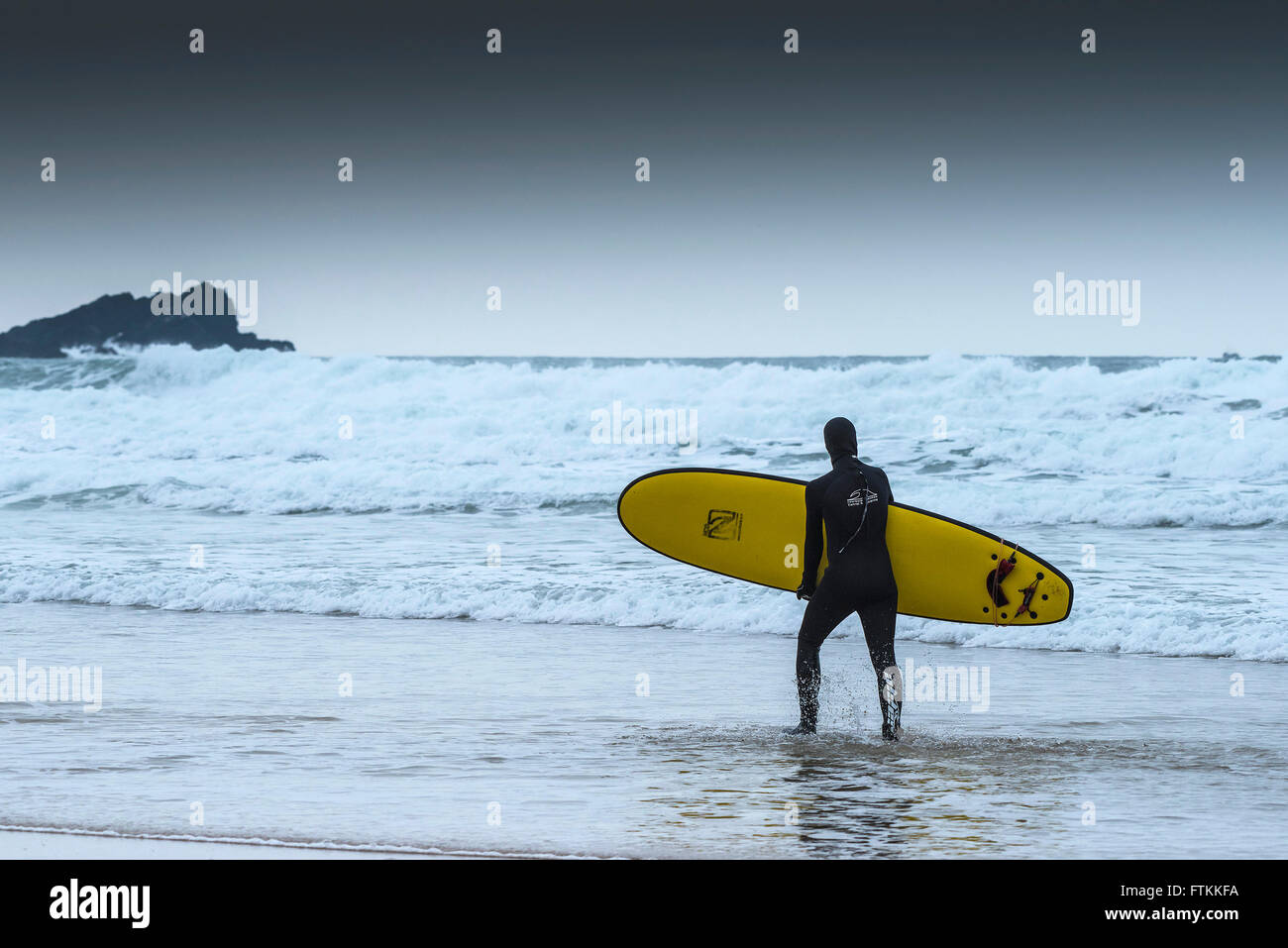 A surfers carries his surboard out to the sea on a cold, chilly day at Fistral Beach in Newquay, Cornwall. - Stock Image