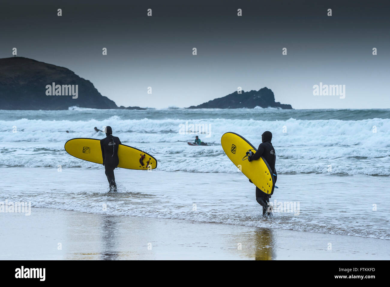 Two surfers carry their surfboards out to sea on a cold, chilly day at Fistral Beach in Newquay, Cornwall. - Stock Image