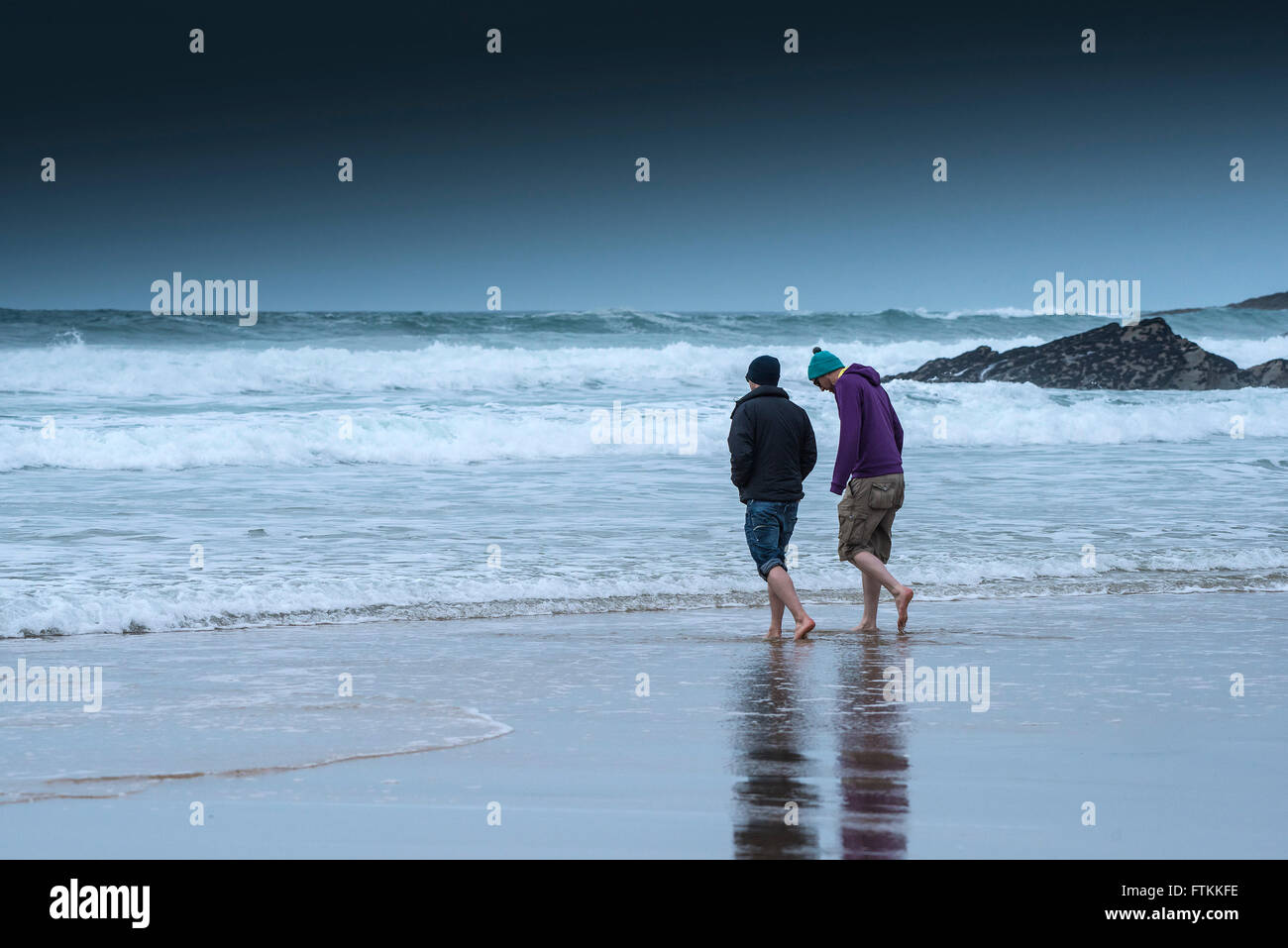 Two friends go for a paddle on a cold, chilly day at Fistral Beach in Newquay, Cornwall. - Stock Image
