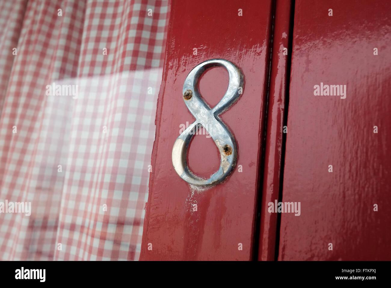 number 8 on red beach hut door - Stock Image