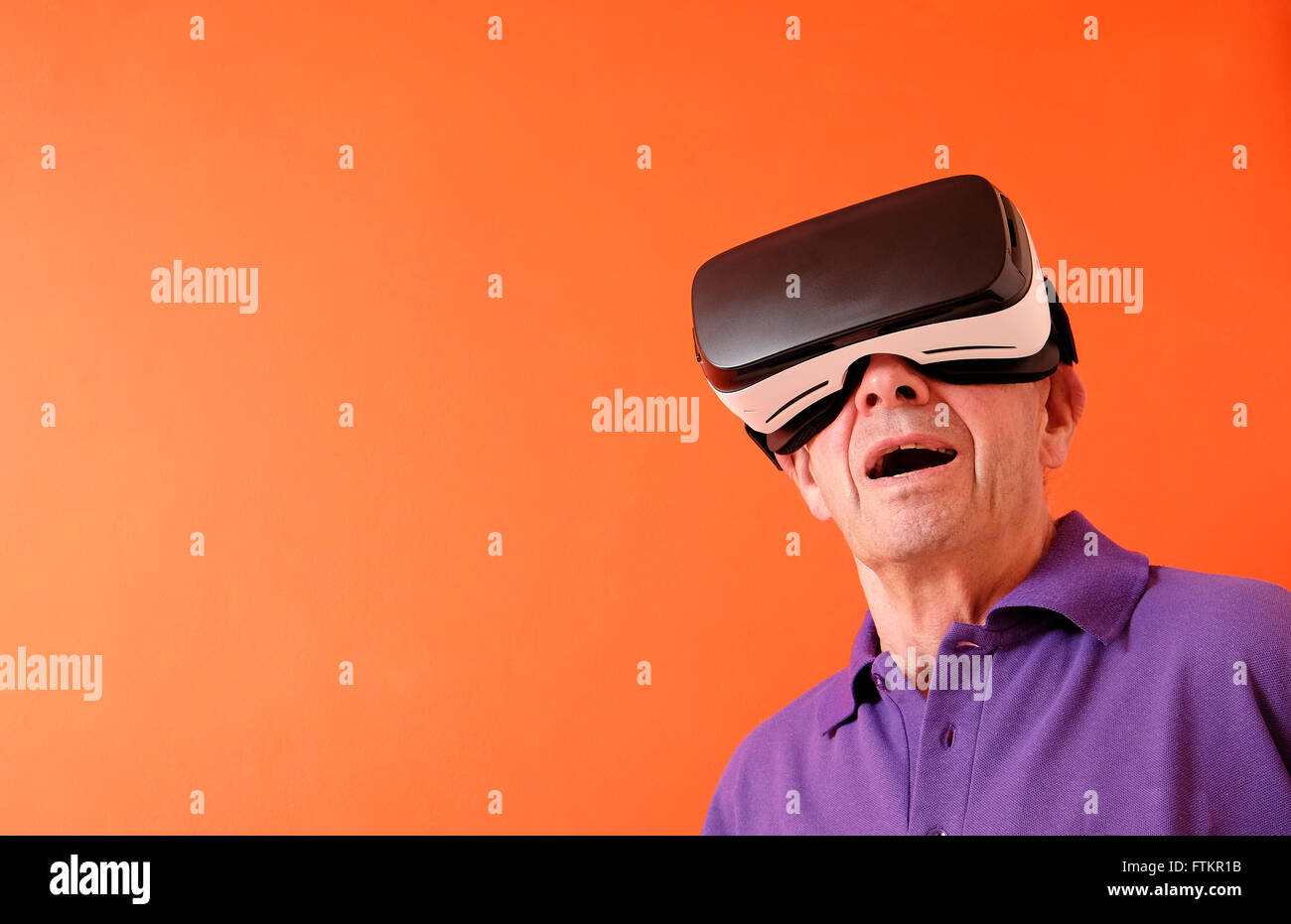virtual reality headset worn by senior man - Stock Image