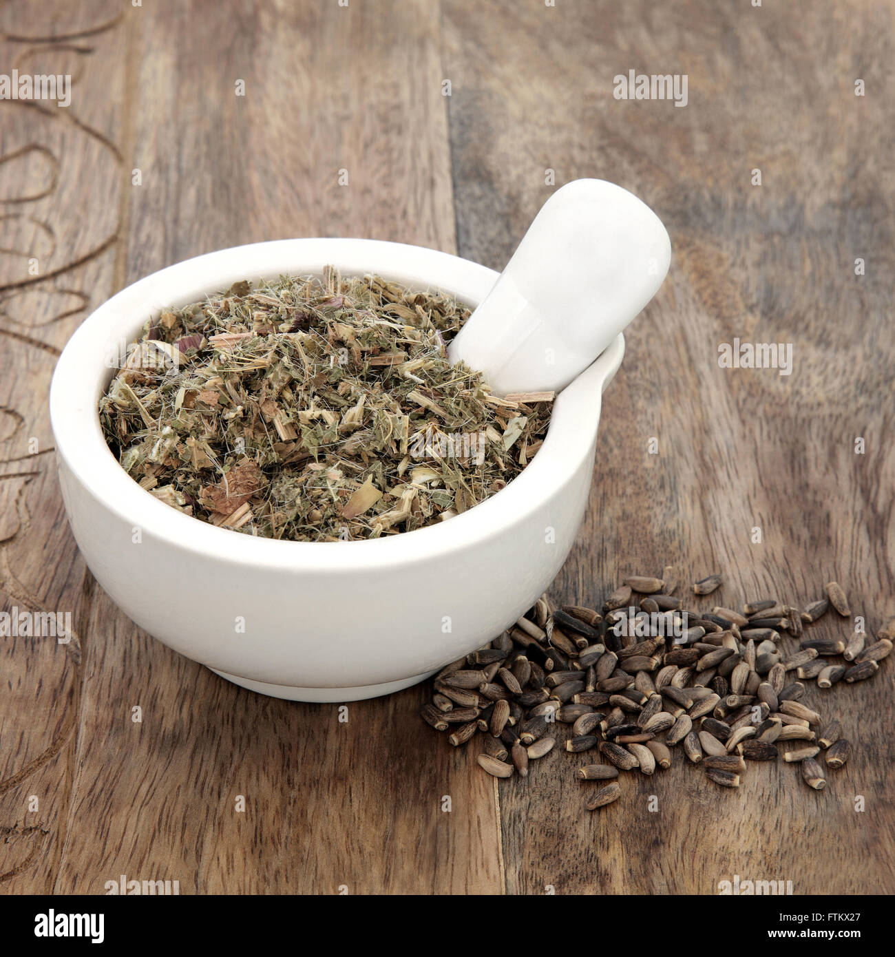 Blessed and milk thistle herb seeds used in natural alternative herbal medicine with mortar and pestle over old - Stock Image