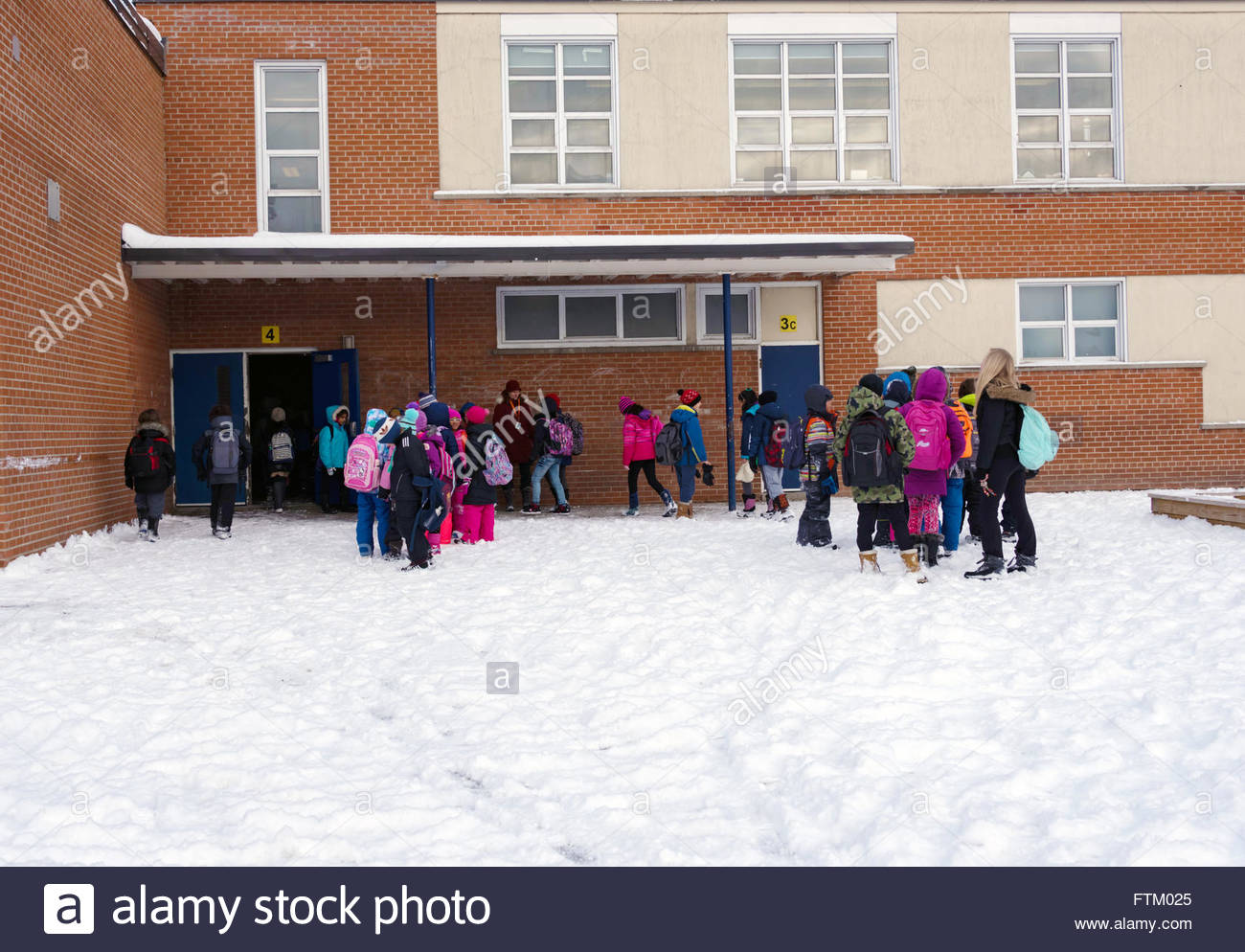 Toronto, Canada, Winter school day, school students waiting about to enter classrooms at a snowy schoolyard. - Stock Image