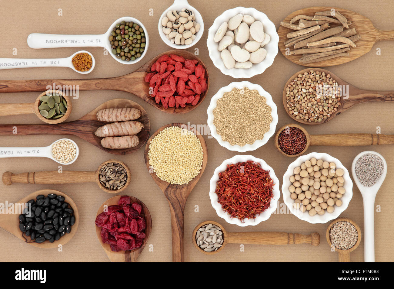 Dried super food selection in spoons and bowls over natural paper background. - Stock Image
