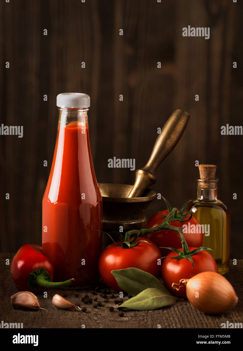 Dark still life with ketchup and ingredients on the rough wood - Stock Image
