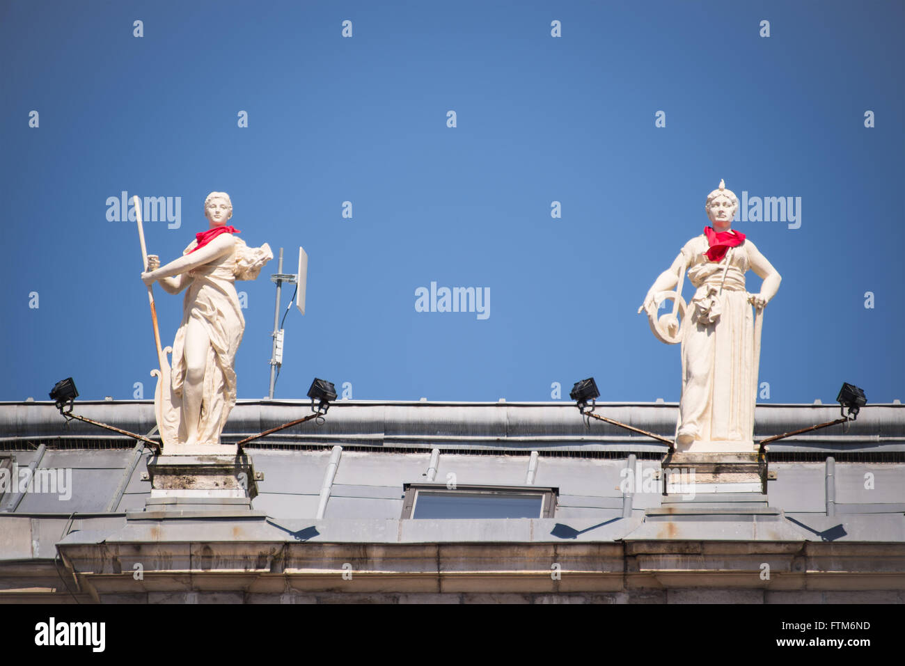 Statues on the roof of the city hall of Bayonne with a red scarf during the Summer festival (Fetes de Bayonne), - Stock Image