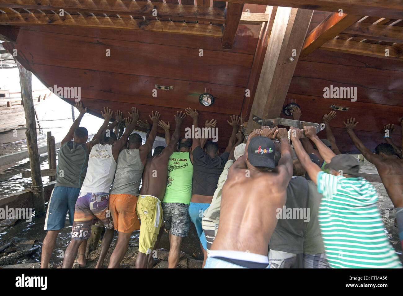Handmade shipyard workers schooners push for water newly built vessel - Stock Image