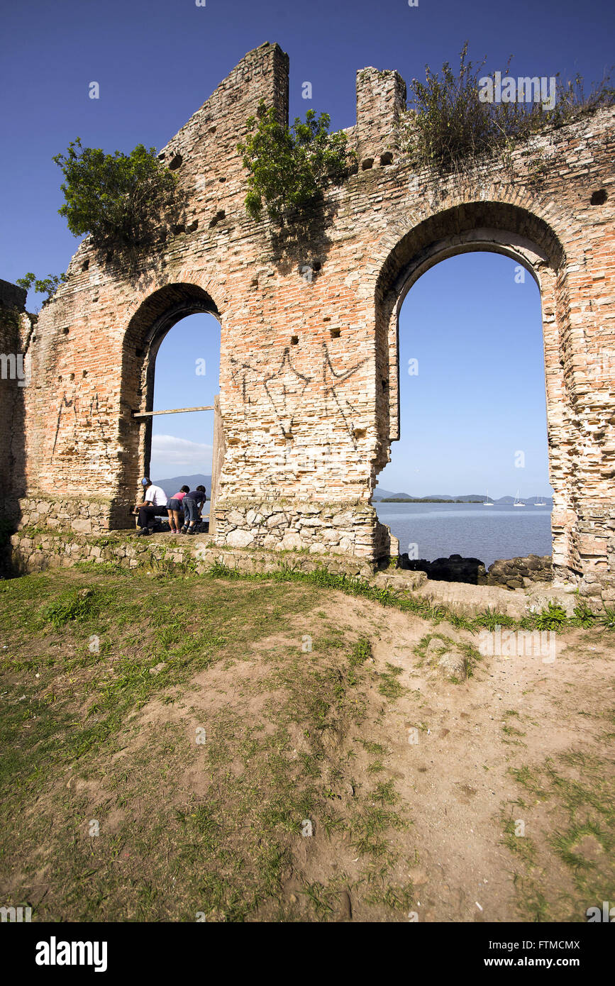 Tourists on the ancient ruins of the house from the Warehouse Macedo on the edge of Paranagua Bay - Stock Image