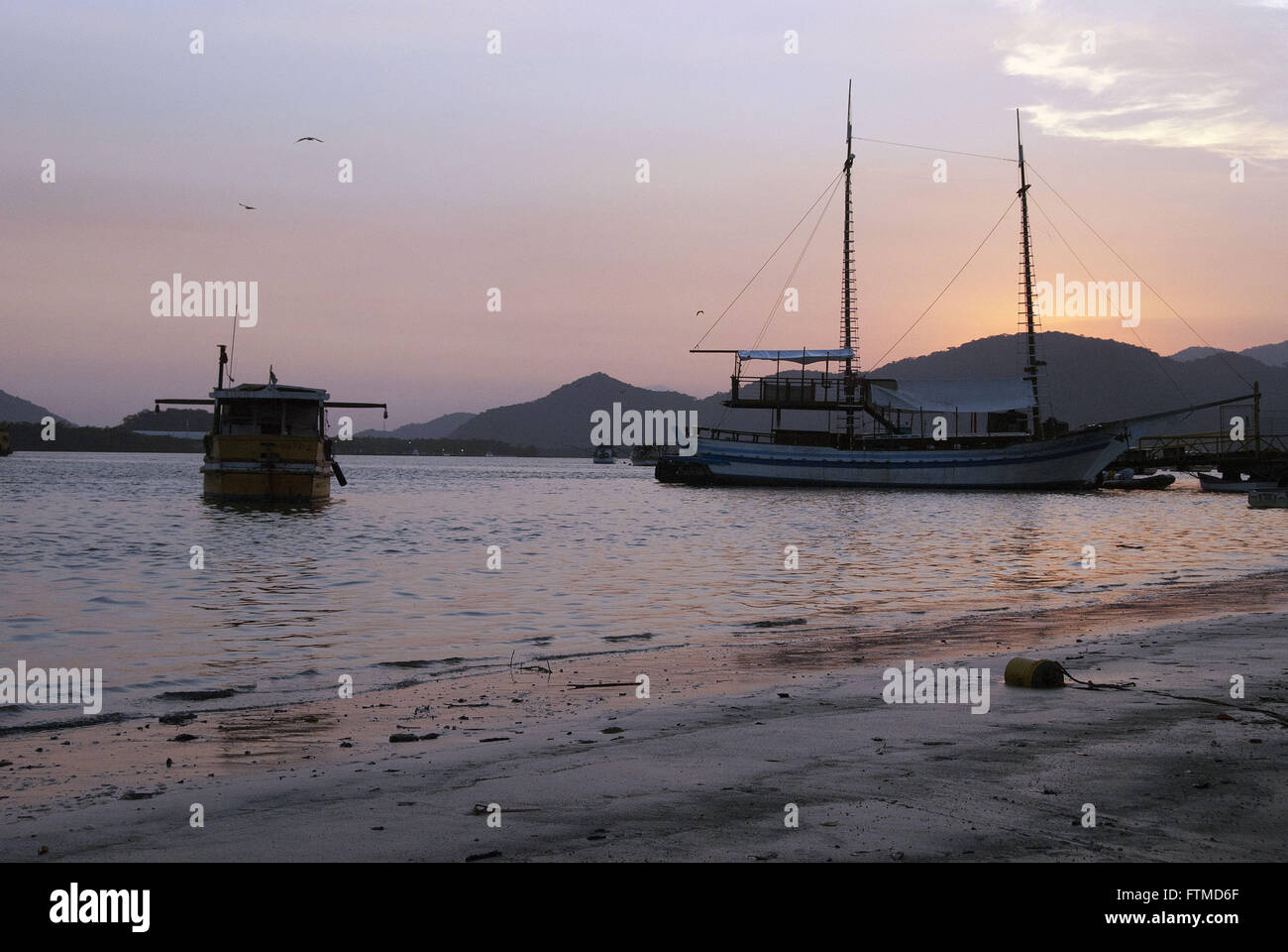 Sunset Bertioga Channel with anchored schooner - Stock Image