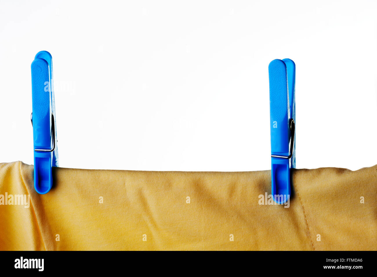 Blue plastic clothes peg or pin securing a yellow t-shirt on clothes line. - Stock Image