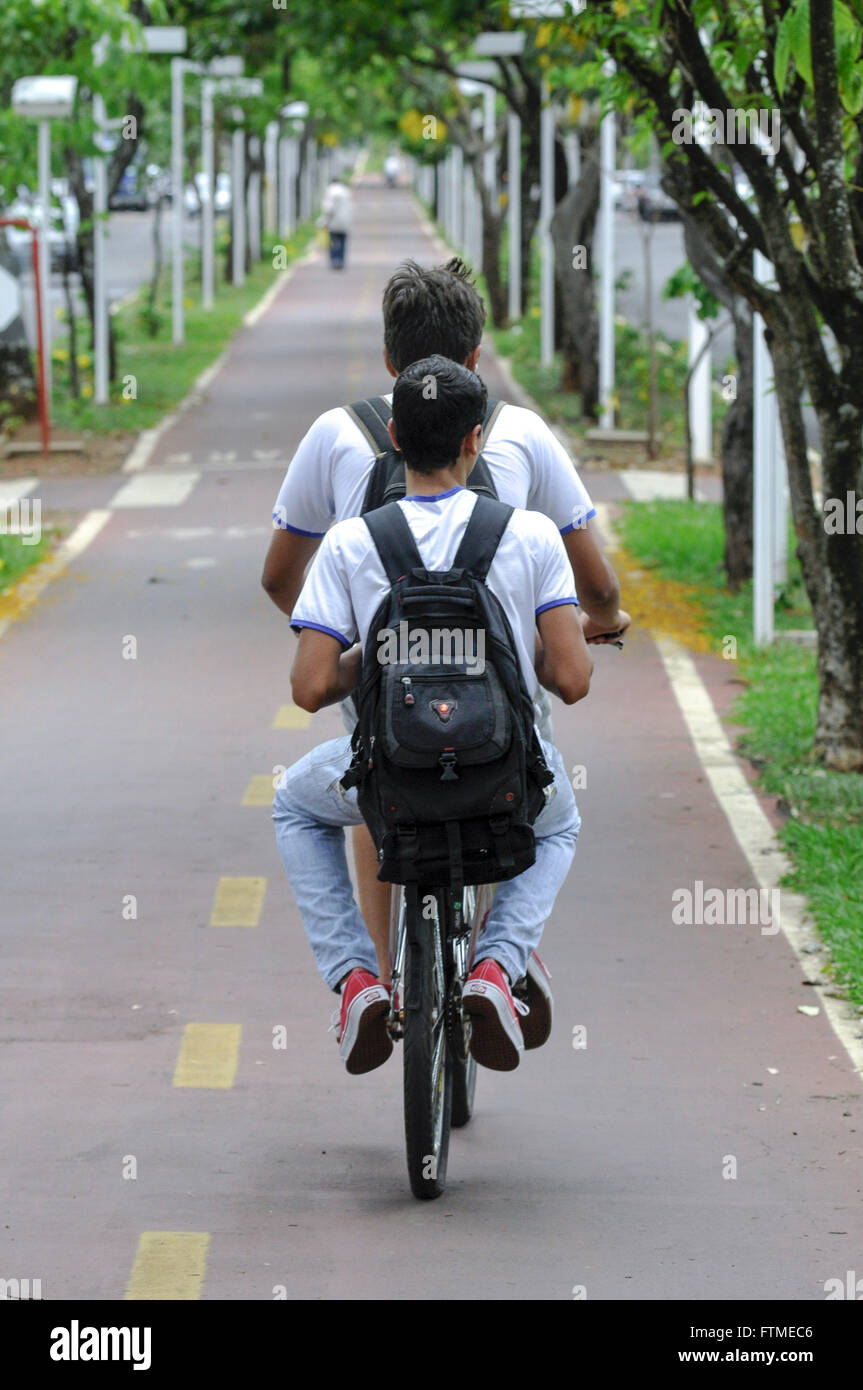 Boy pillion bike in bike lane in the median of North Avenue Brazil - Stock Image