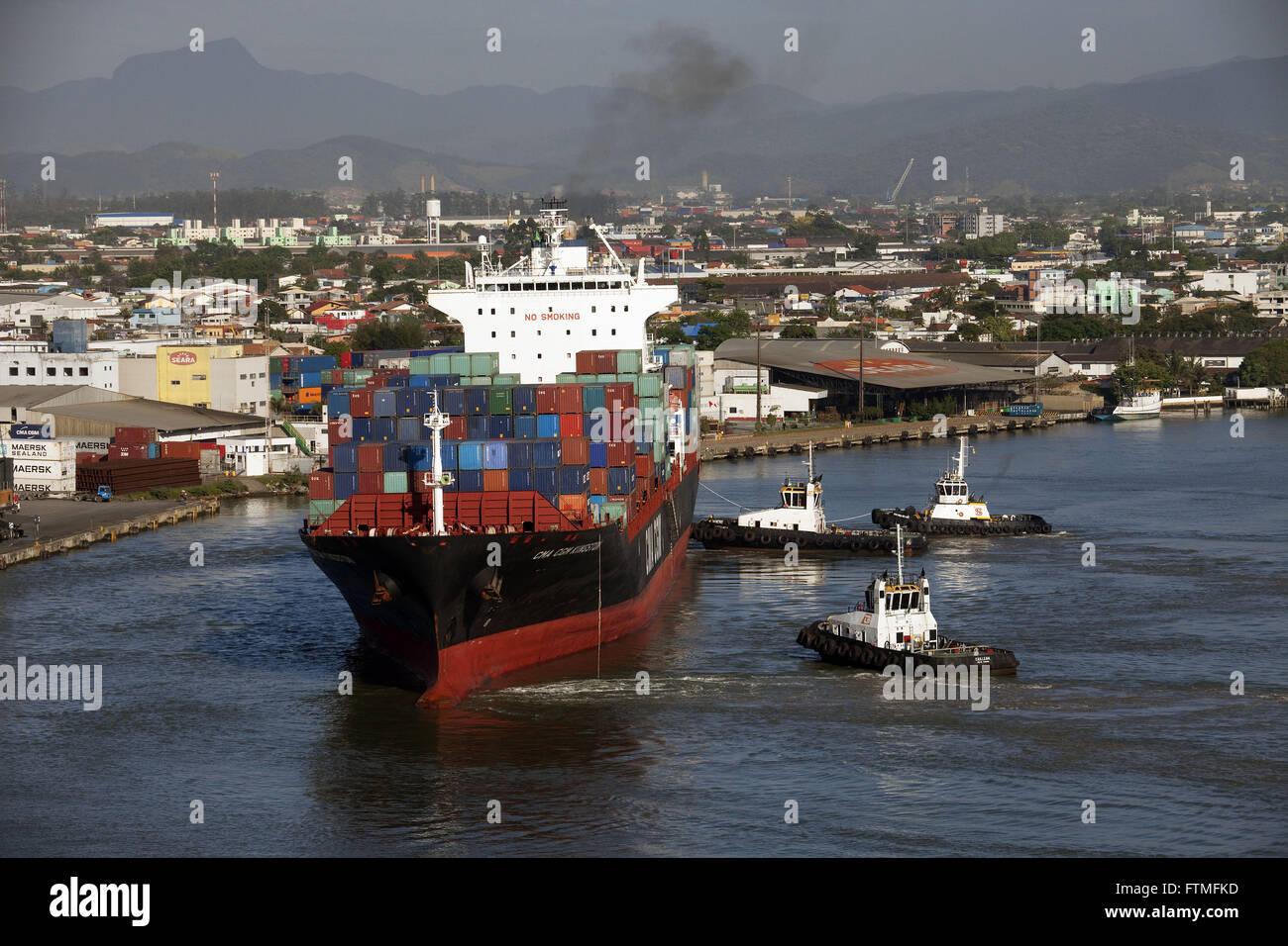 Cargo ship leaving the port of Itajai followed by tugs - Stock Image