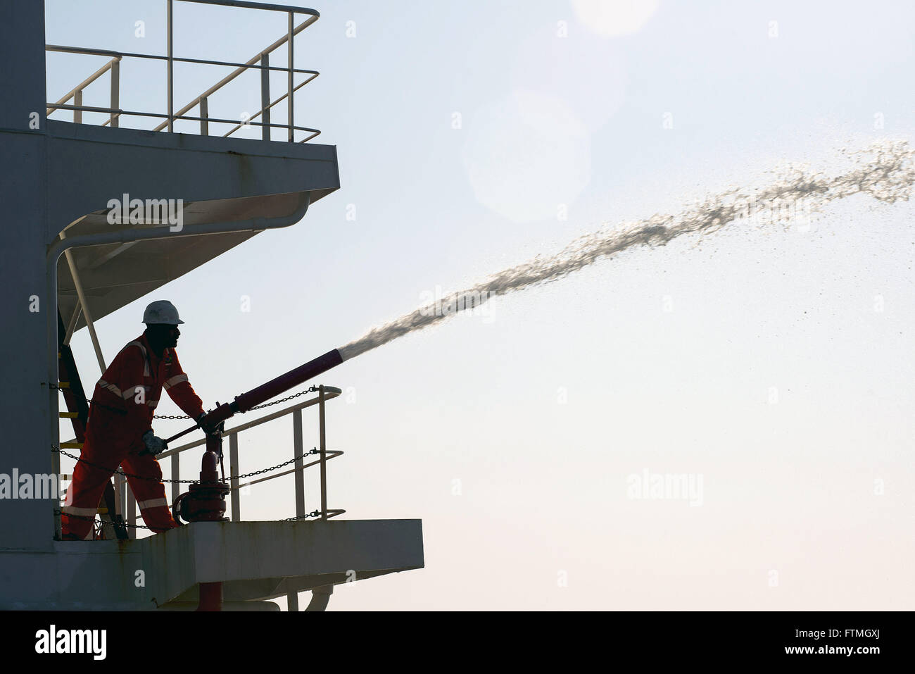 Foreman handles cannon fire fighting ship Maisa - Stock Image