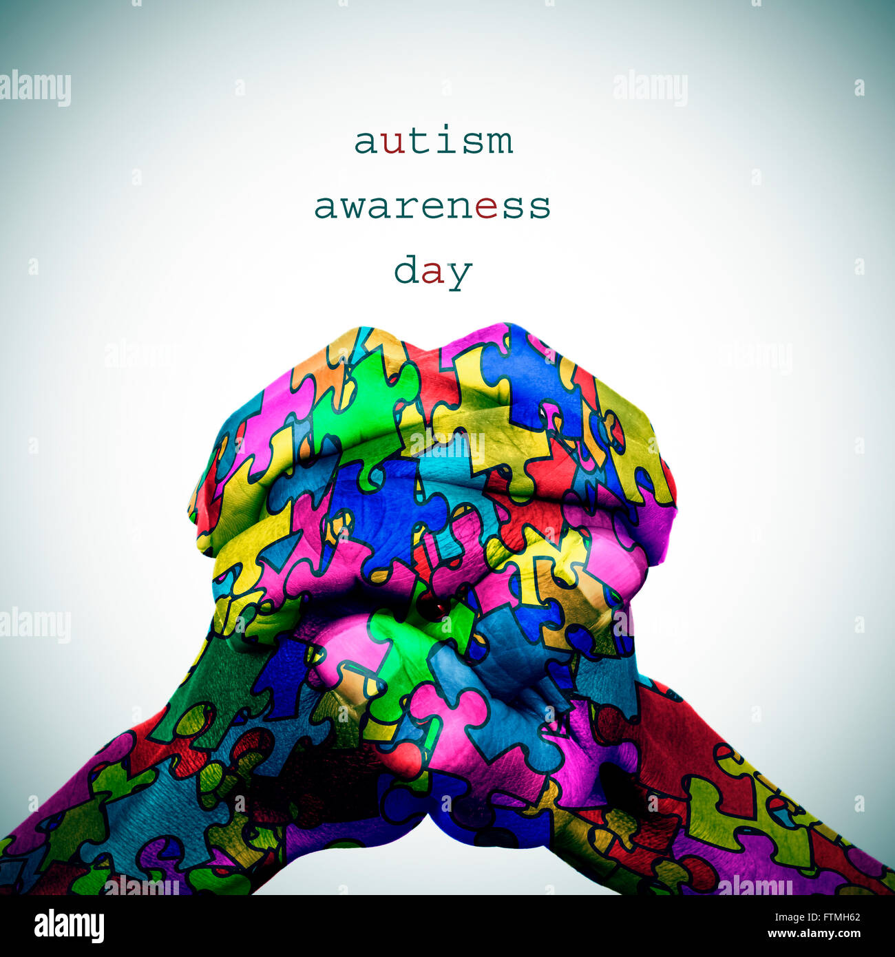 text autism awareness day and the hands of a man put together patterned with many puzzle pieces of different colors, - Stock Image