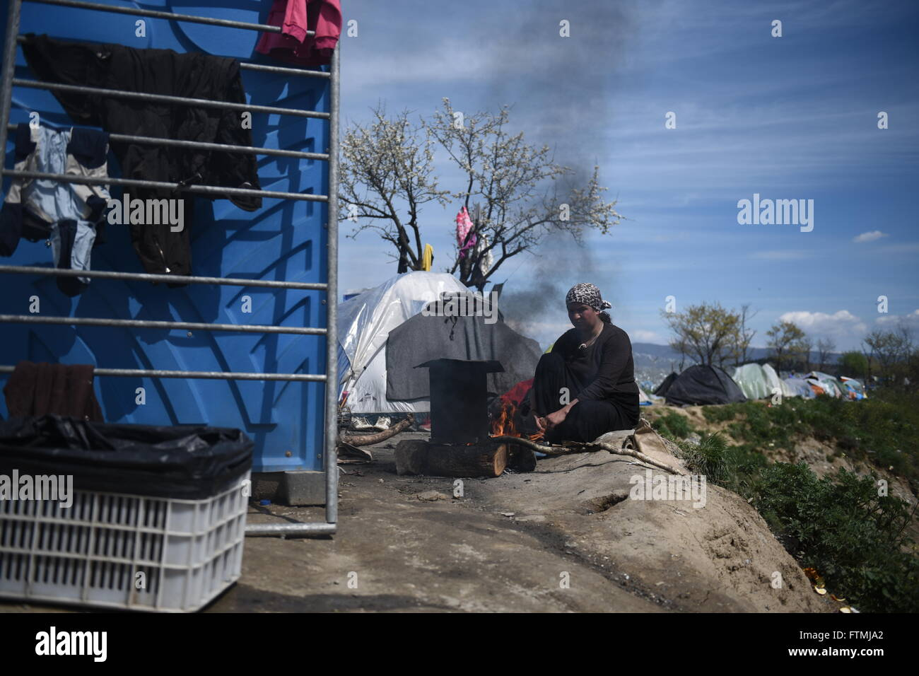 A woman sits near a fire, as refugees and migrants remain stranded at the closed Greek Macedonian border, near the - Stock Image