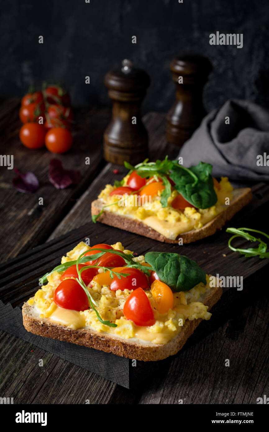 Toast for breakfast with scrambled eggs, cheese, cherry tomatoes, arugula and corn salad on rustic wooden background Stock Photo