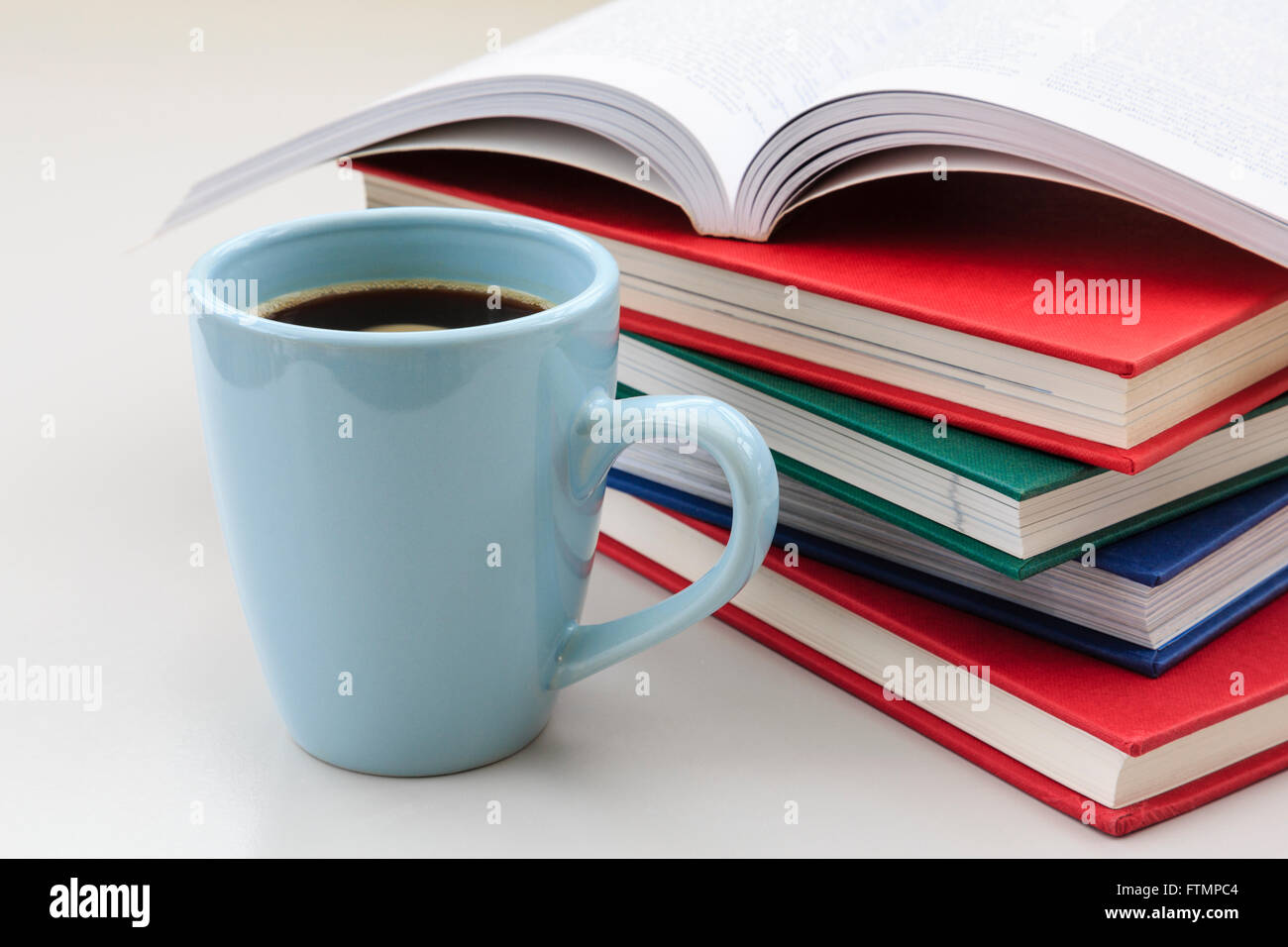 Student's study scene with pile of books on a desk with a mug of strong black coffee to help stay awake for - Stock Image