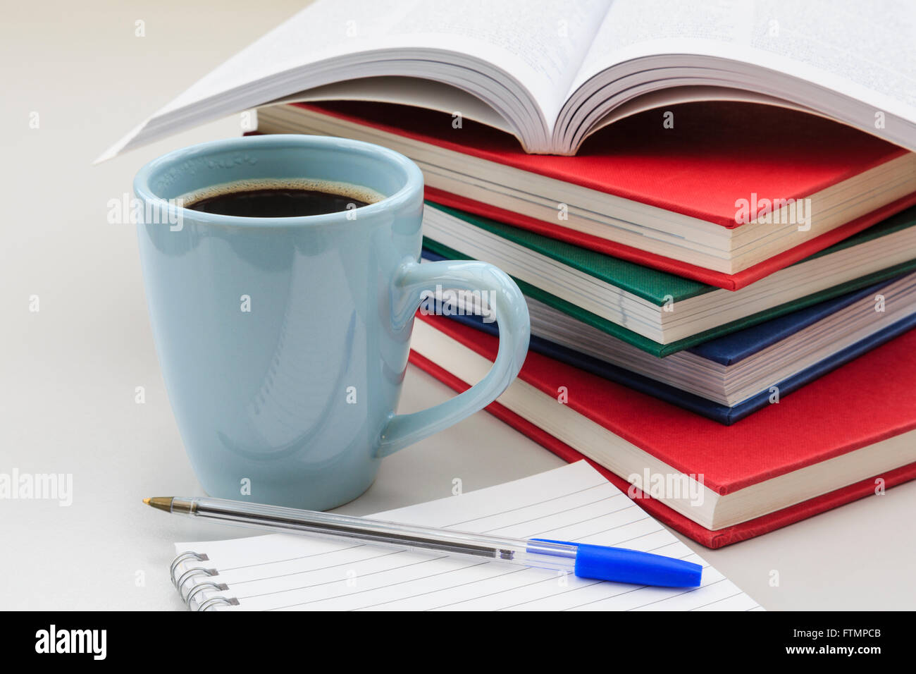 Student's study scene with pile of books and mug of strong black coffee by a notebook and pen on a desk for - Stock Image